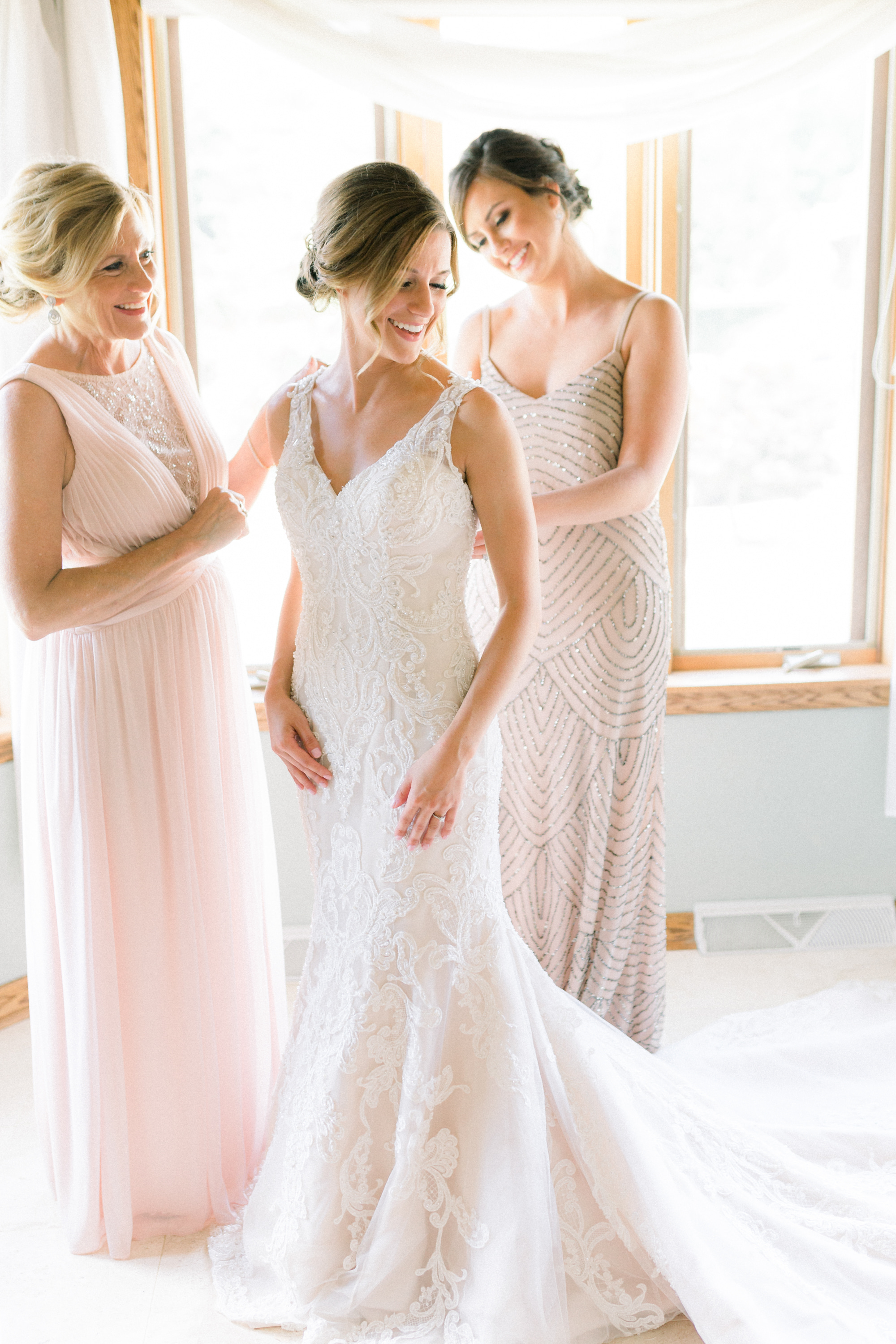 Bride getting into wedding dress for Pittsburgh wedding planned by Exhale Events. Find more wedding inspiration at exhale-events.com!