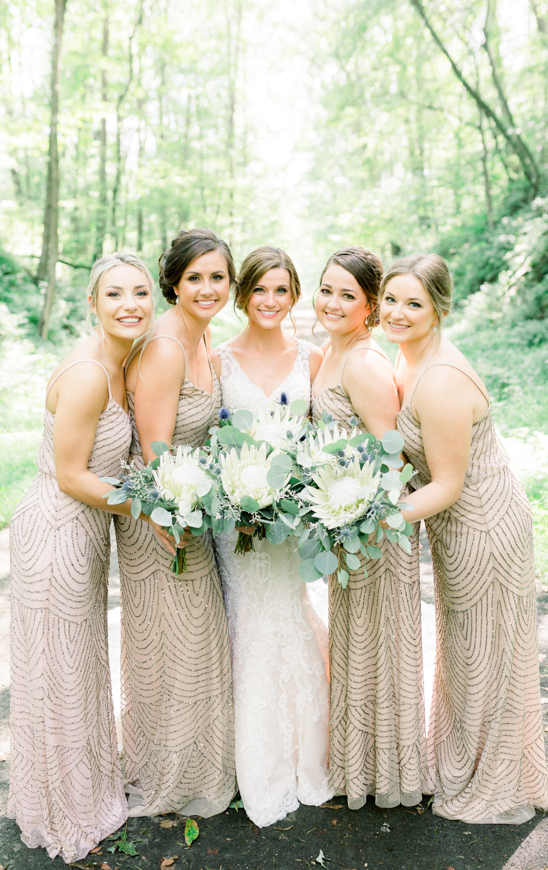 Bride and bridesmaids in Adrianna Papell dresses take wedding photos for Pittsburgh wedding planned by Exhale Events. Find more wedding inspiration at exhale-events.com!