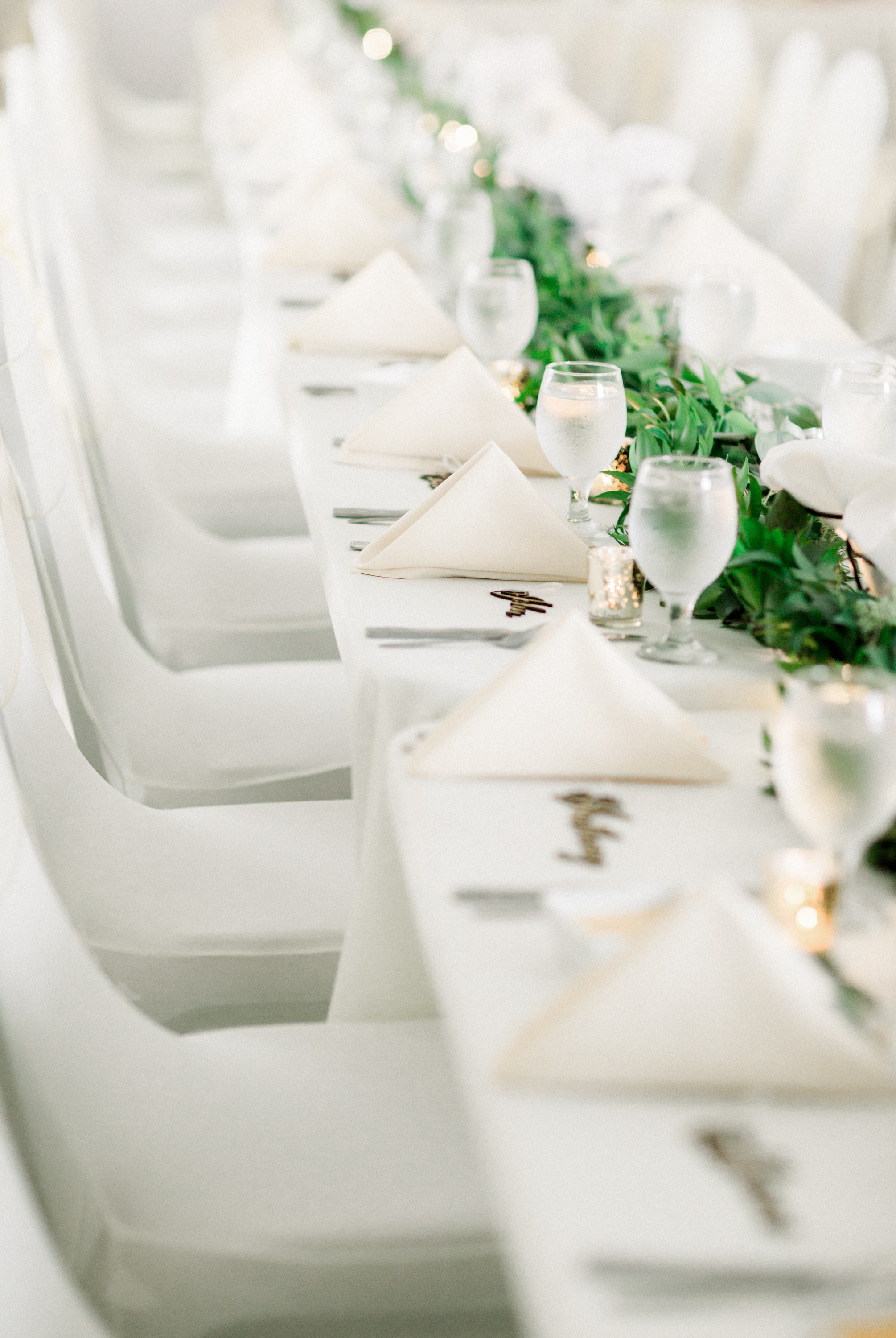 Wedding table decor with greenery table runner and lazer-cut escort cards for Pittsburgh wedding planned by Exhale Events. Find more wedding inspiration at exhale-events.com!
