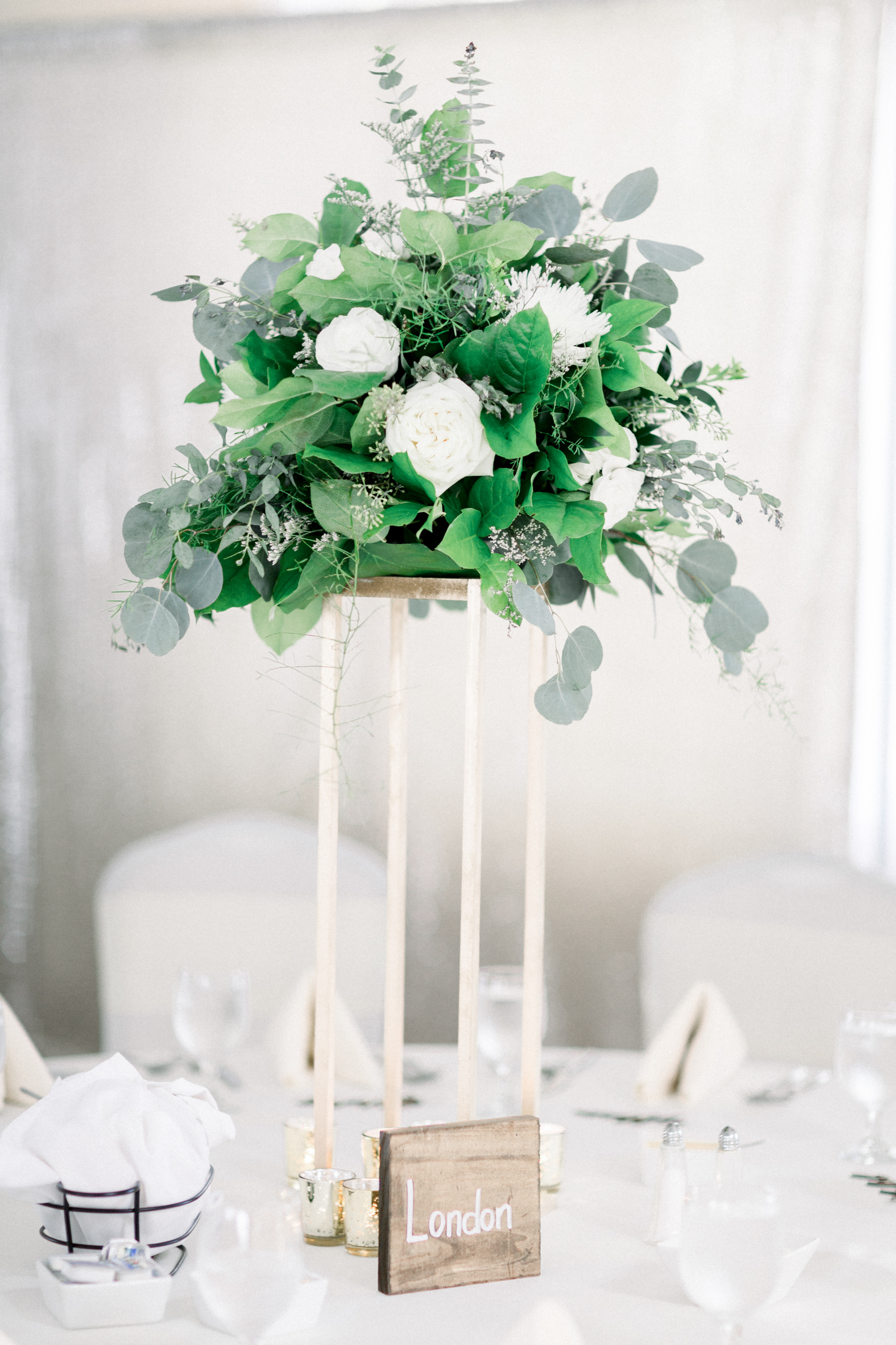Greenery, eucalyptus, and white roses tall wedding centerpieces for Pittsburgh wedding planned by Exhale Events. Find more wedding inspiration at exhale-events.com!