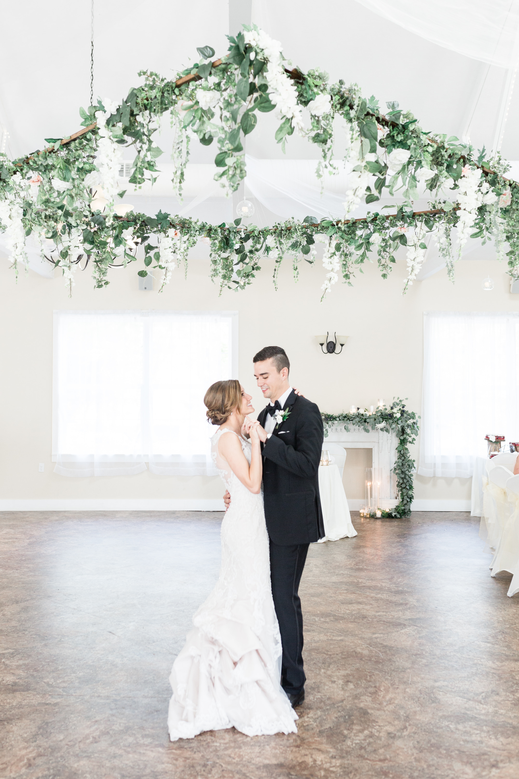 Bride and groom share first dance under DIY hanging floral wreath at Pittsburgh wedding planned by Exhale Events. Find more wedding inspiration at exhale-events.com!