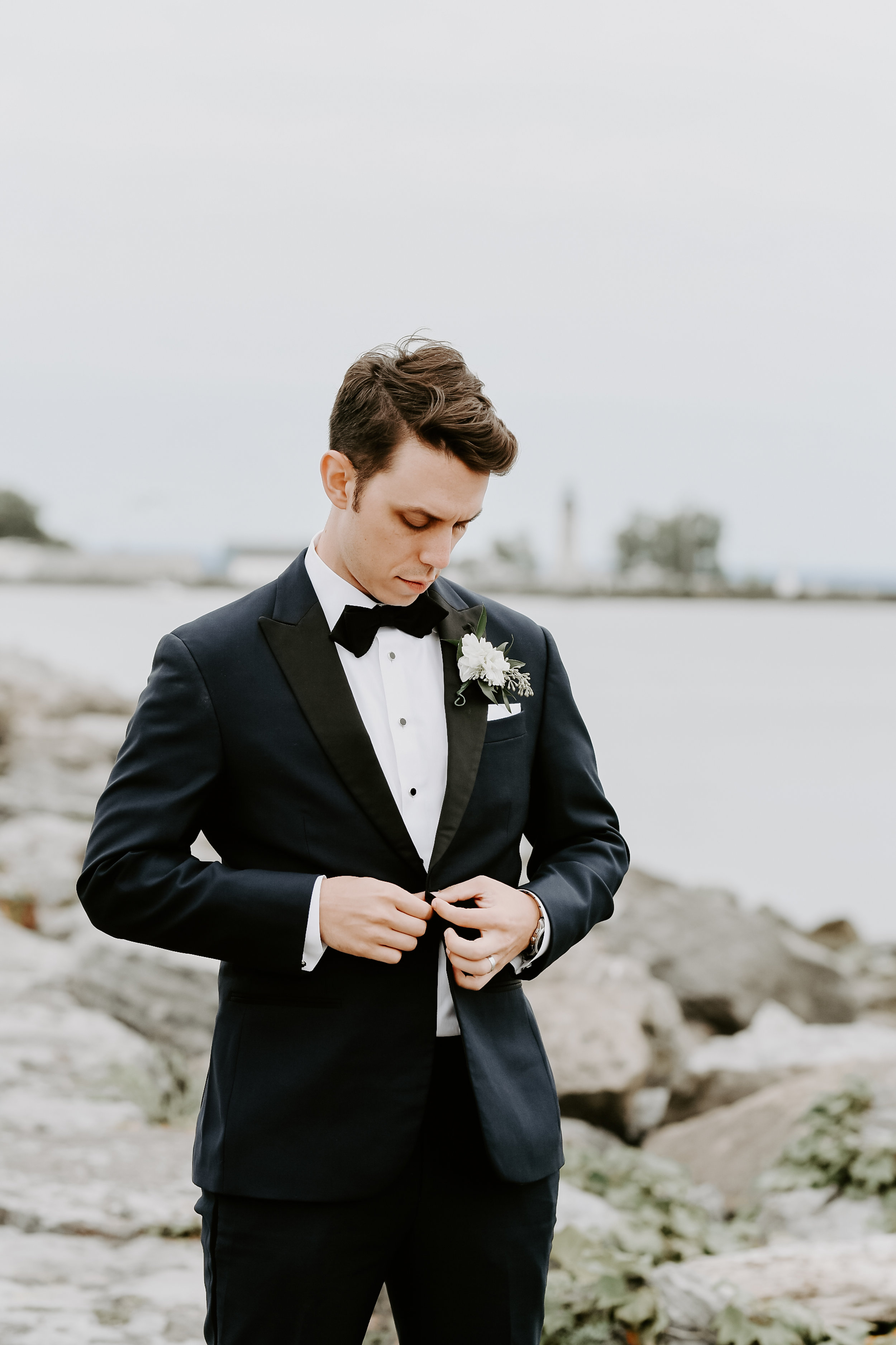 Groom poses modern tuxedo for wedding photos at Buffalo, NY wedding planned by Exhale Events. Find more wedding inspiration at exhale-events.com!