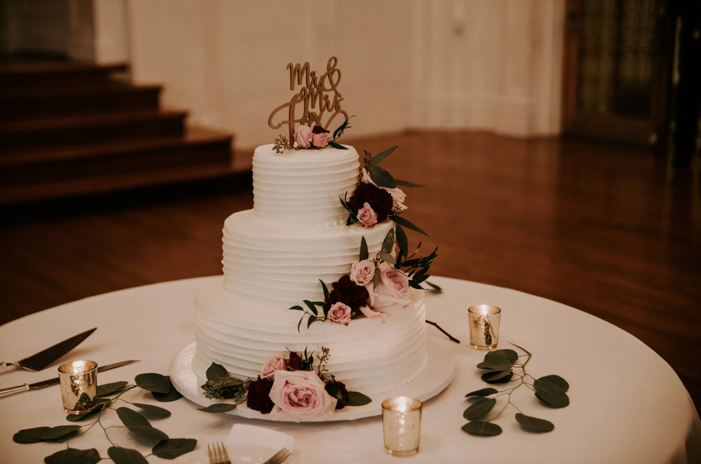 Wedding cake with flowers and gold wedding topper at Buffalo, NY wedding planned by Exhale Events. Find more wedding inspiration at exhale-events.com!