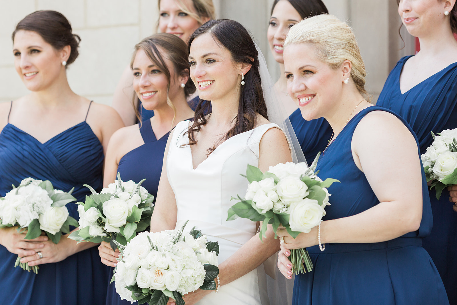 Bride with bridesmaids with blue dresses and white wedding bouquets pose for Pittsburgh wedding at PNC Park planned by Exhale Events. Find more wedding inspiration at exhale-events.com!