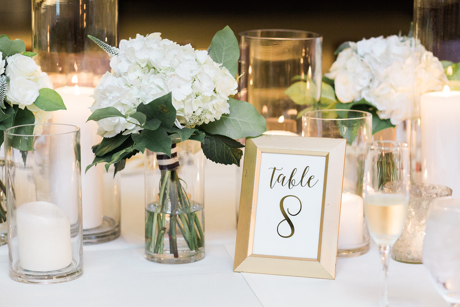 Low wedding centerpieces with white flowers and wedding table numbers in gold frames for Pittsburgh wedding at PNC Park planned by Exhale Events. Find more wedding inspiration at exhale-events.com!