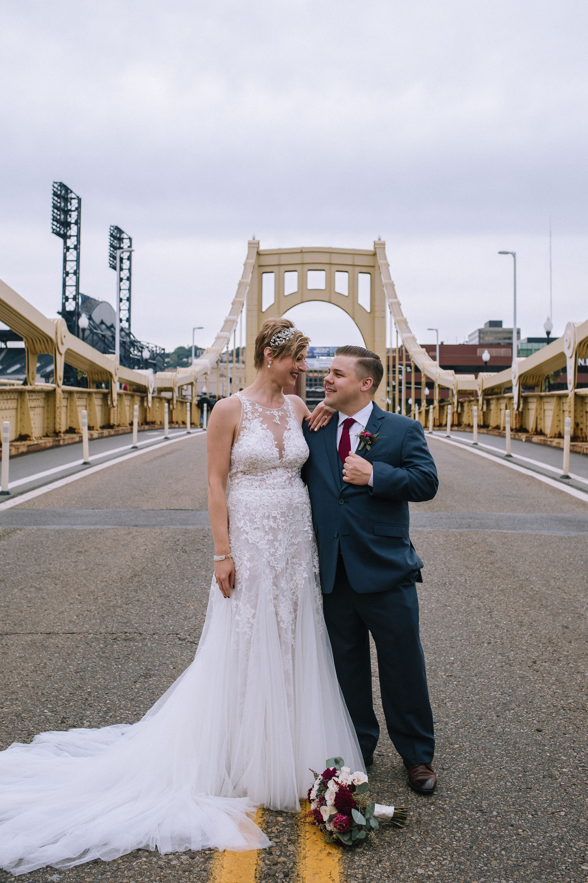 Bride and groom pose for wedding photos on bridge at Pittsburgh wedding at Studio Slate planned by Exhale Events. Find more wedding inspiration at exhale-events.com!