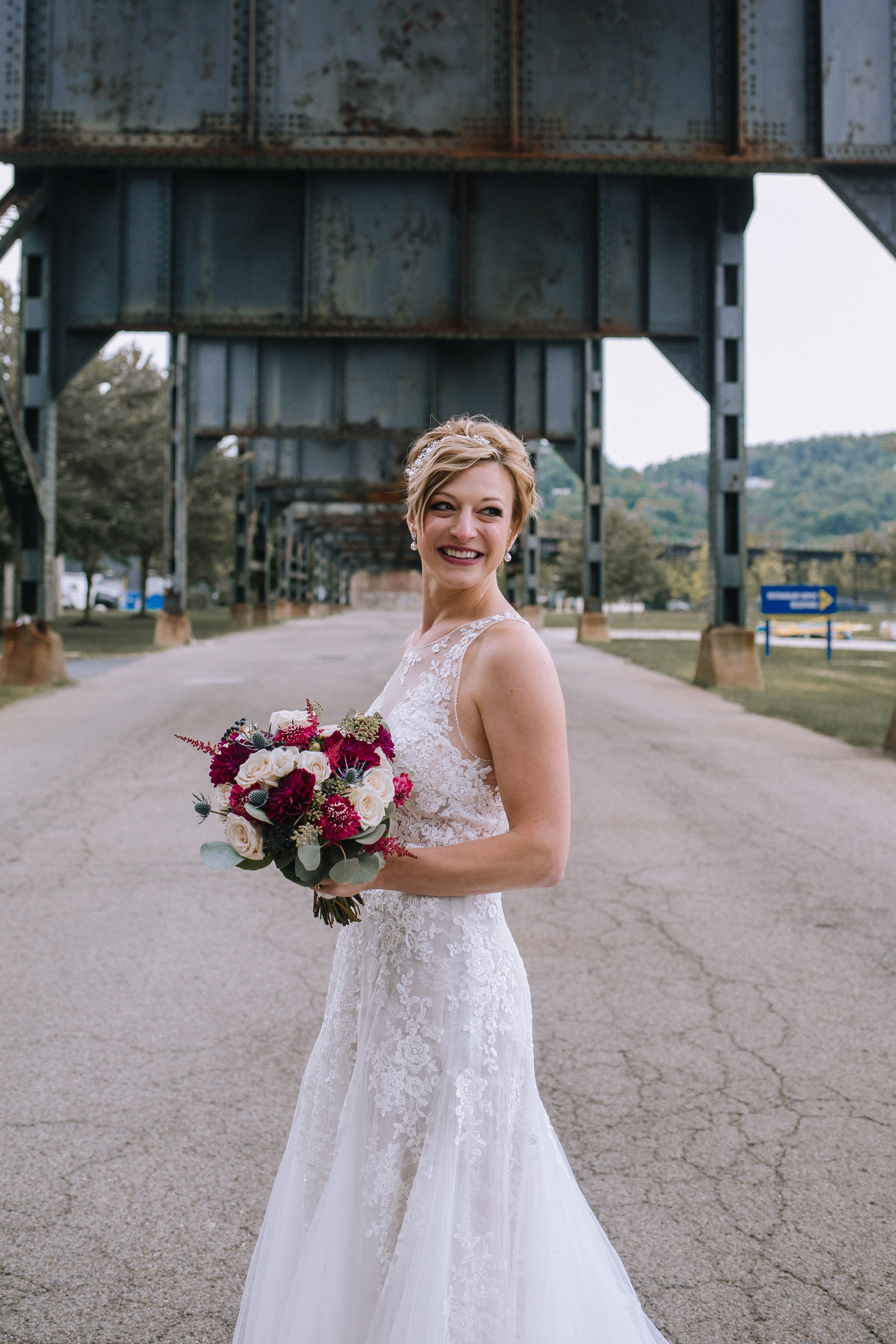 Brides poses in modern wedding dress with red wedding bouquet for Pittsburgh wedding at Studio Slate planned by Exhale Events. Find more wedding inspiration at exhale-events.com!
