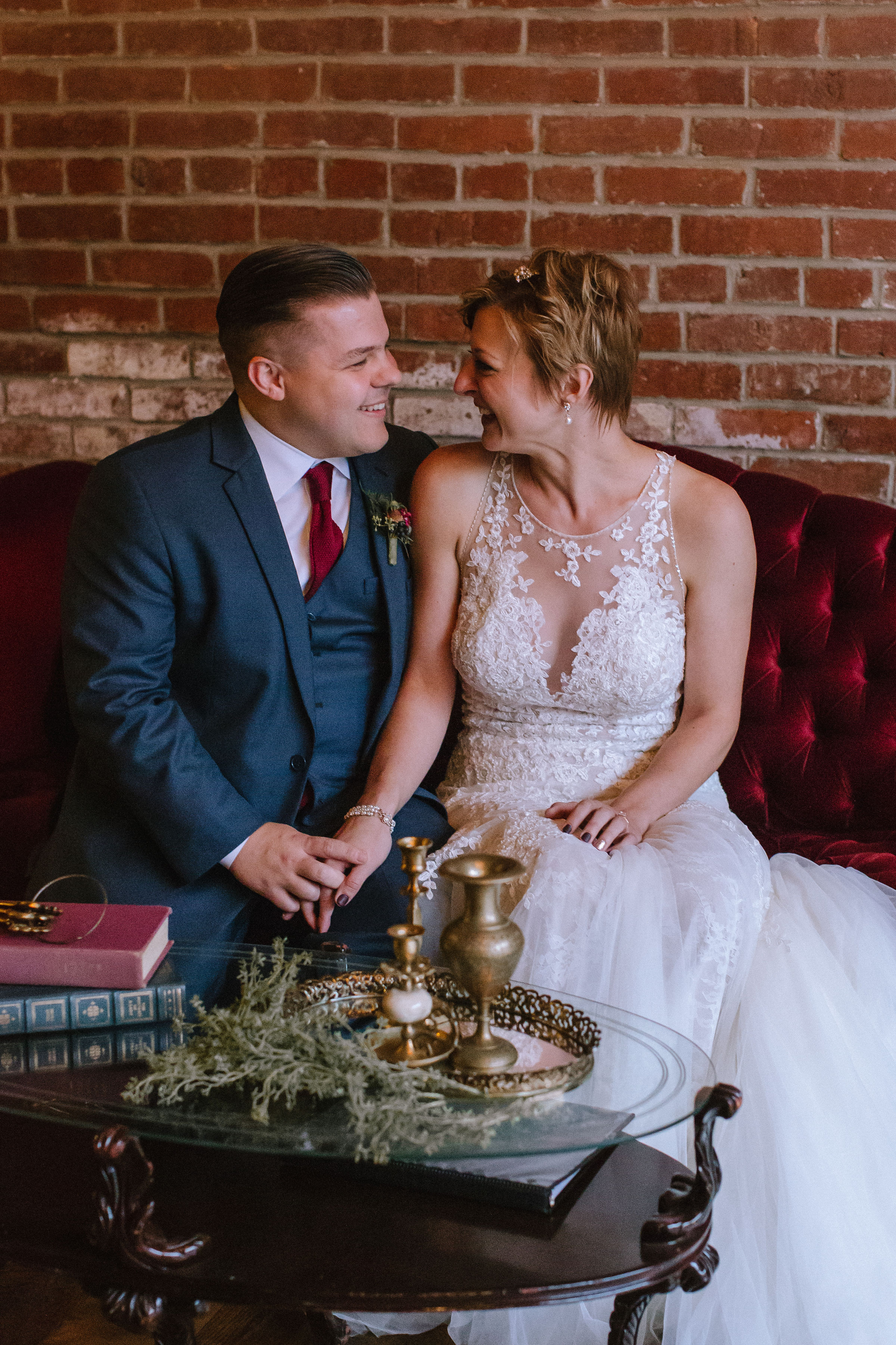Bride and groom pose with vintage wedding reception decor at Pittsburgh wedding at Studio Slate planned by Exhale Events. Find more wedding inspiration at exhale-events.com!