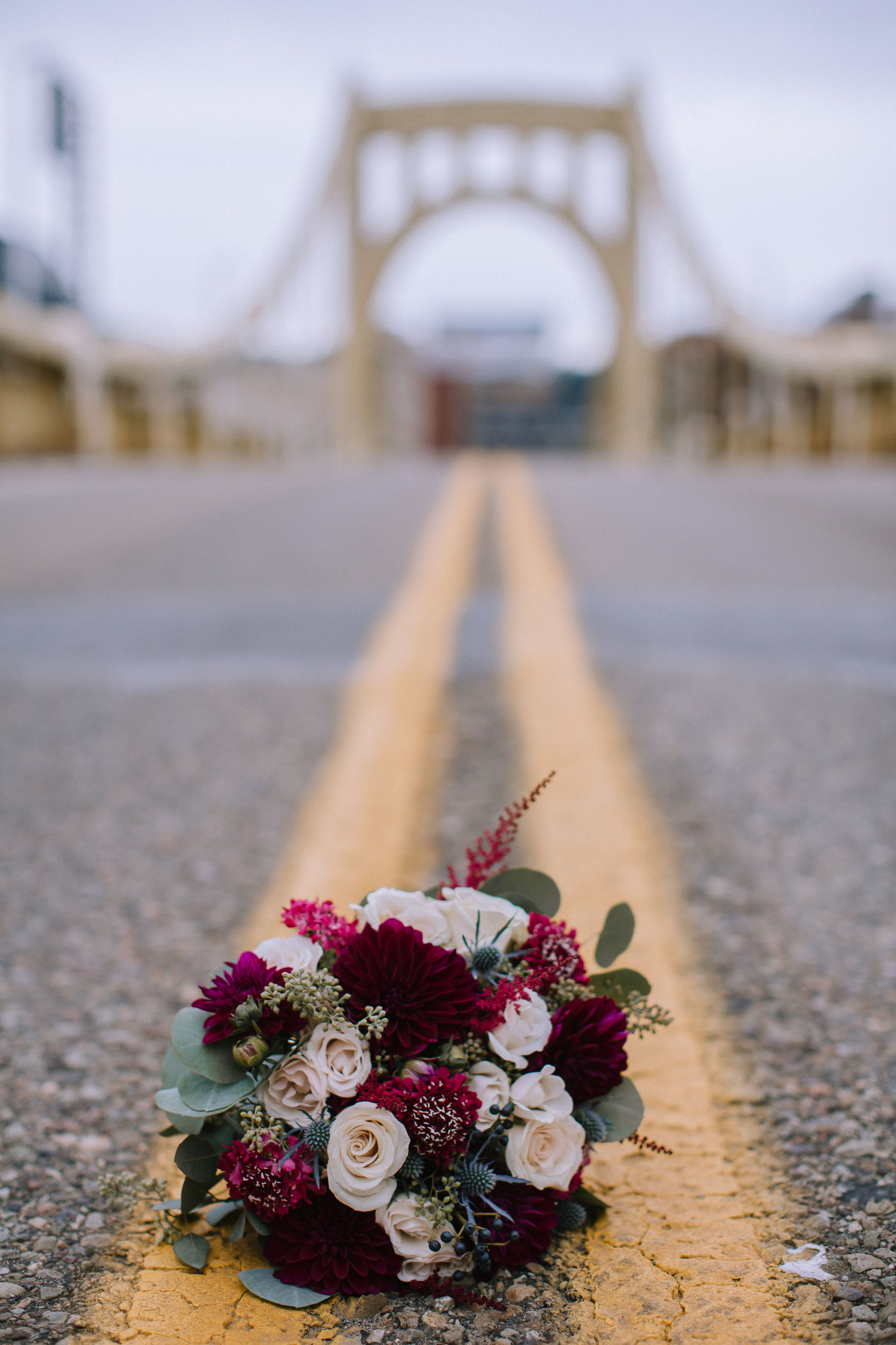 Wedding bouquet on city bridge for Pittsburgh wedding at Studio Slate planned by Exhale Events. Find more wedding inspiration at exhale-events.com!