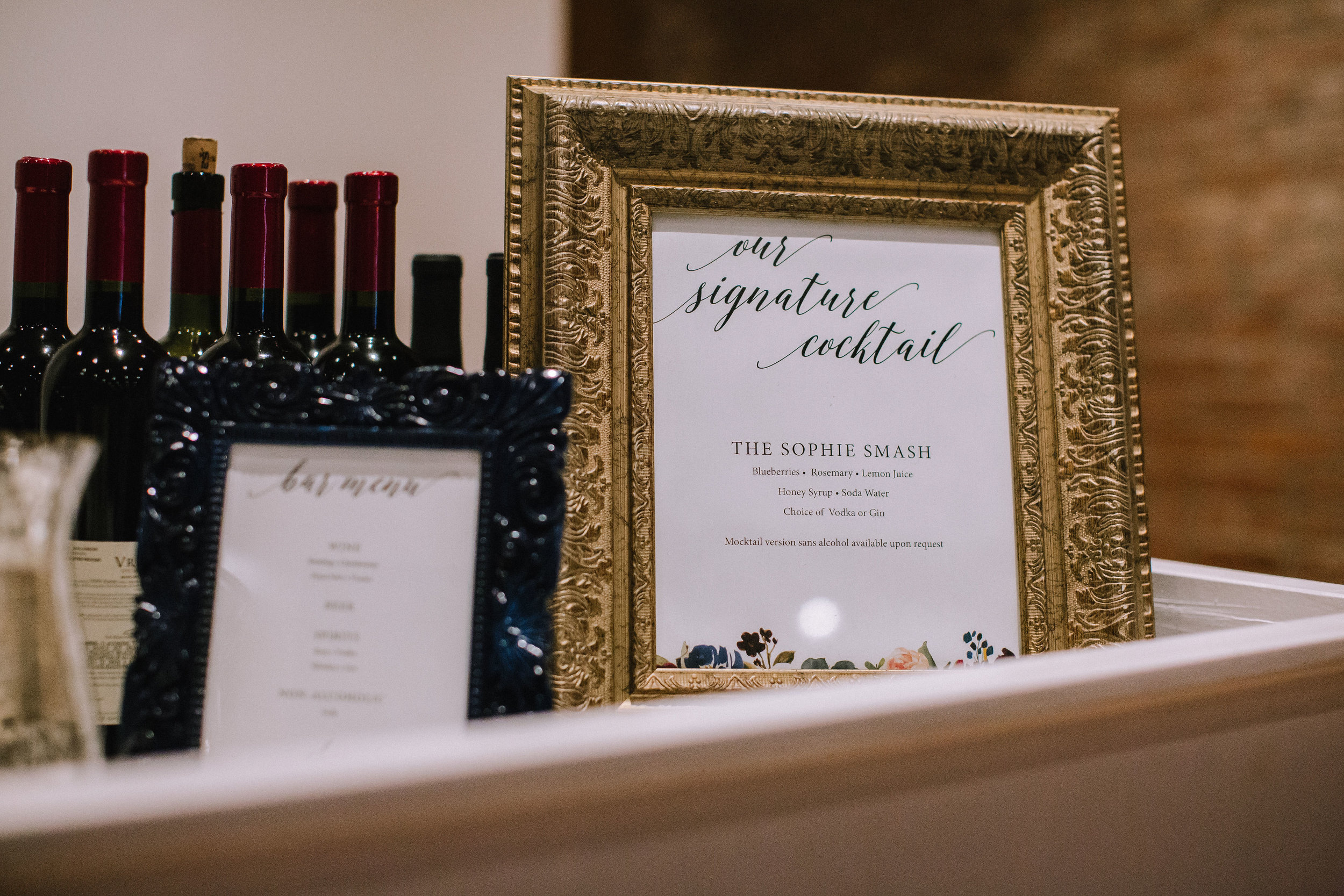Wedding signature drinks displayed in vintage gold frame for Pittsburgh wedding at Studio Slate planned by Exhale Events. Find more wedding inspiration at exhale-events.com!