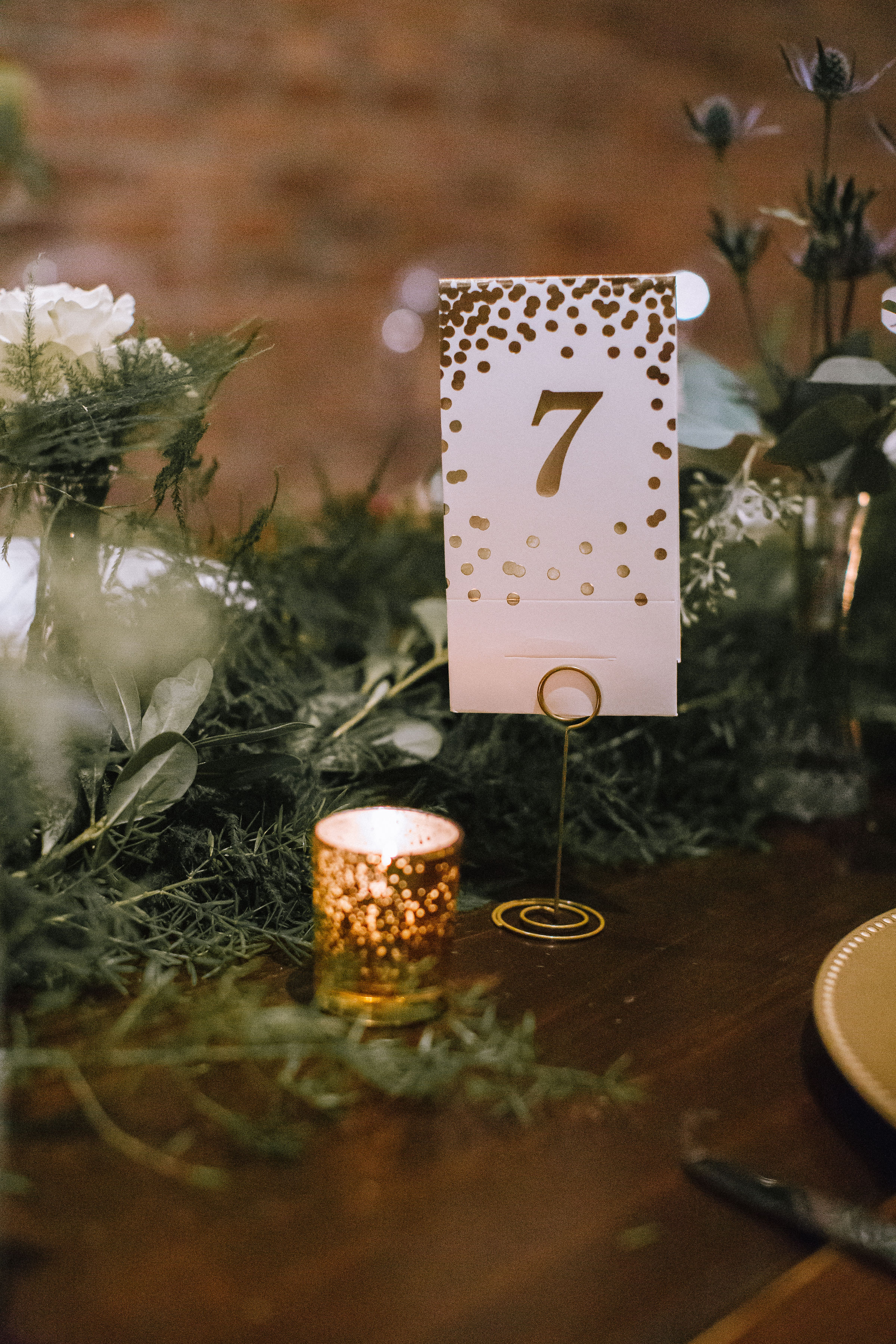 Gold wedding table numbers placed on wedding table with greenery and candles for Pittsburgh wedding at Studio Slate planned by Exhale Events. Find more wedding inspiration at exhale-events.com!
