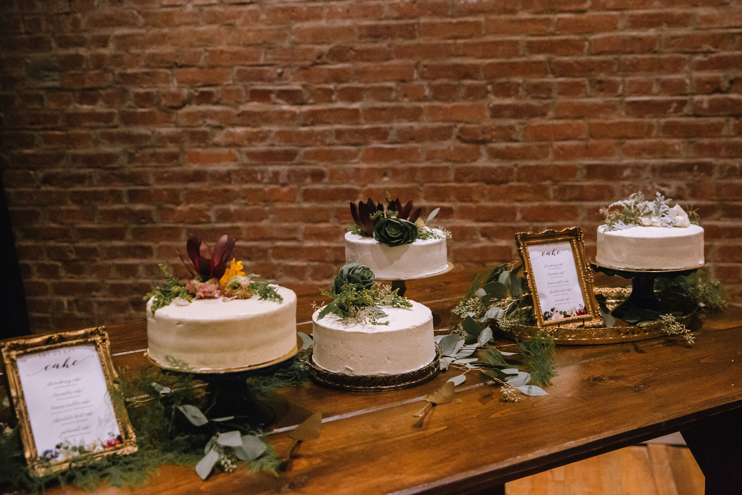 Multiple one-tier wedding cakes on wedding cake and dessert table for Pittsburgh wedding at Studio Slate planned by Exhale Events. Find more wedding inspiration at exhale-events.com!