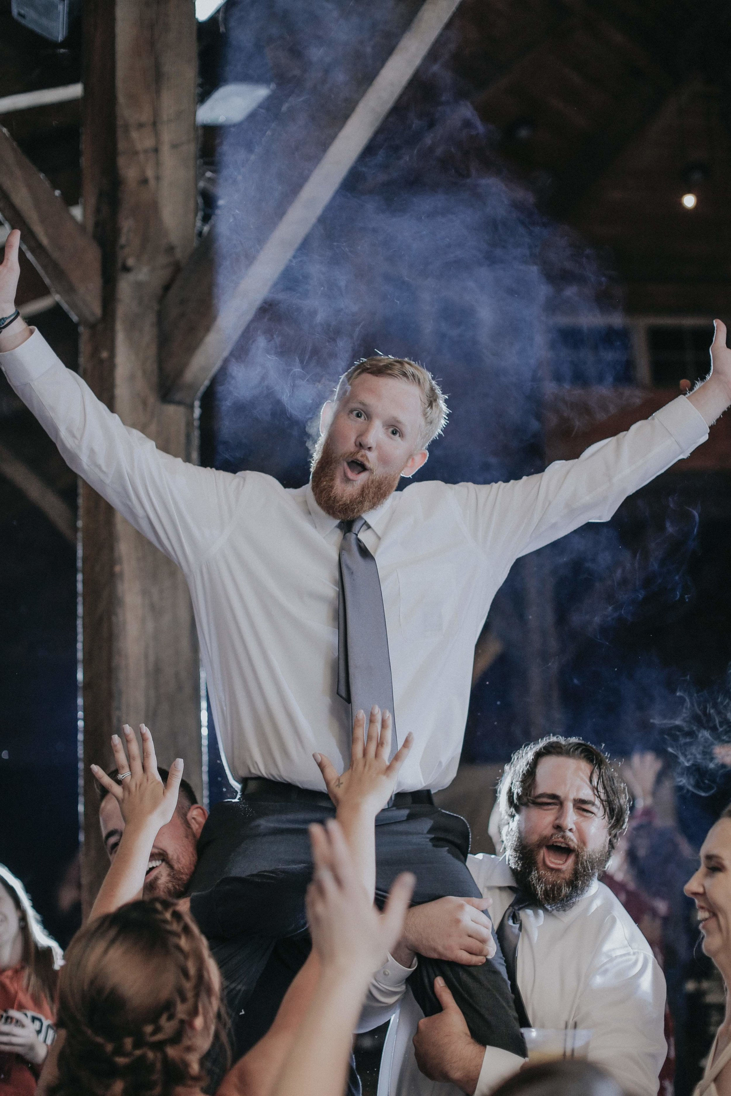 Groom celebrating at wedding reception at rustic wedding in Farmington, PA planned by Exhale Events. Find more wedding inspiration at exhale-events.com!