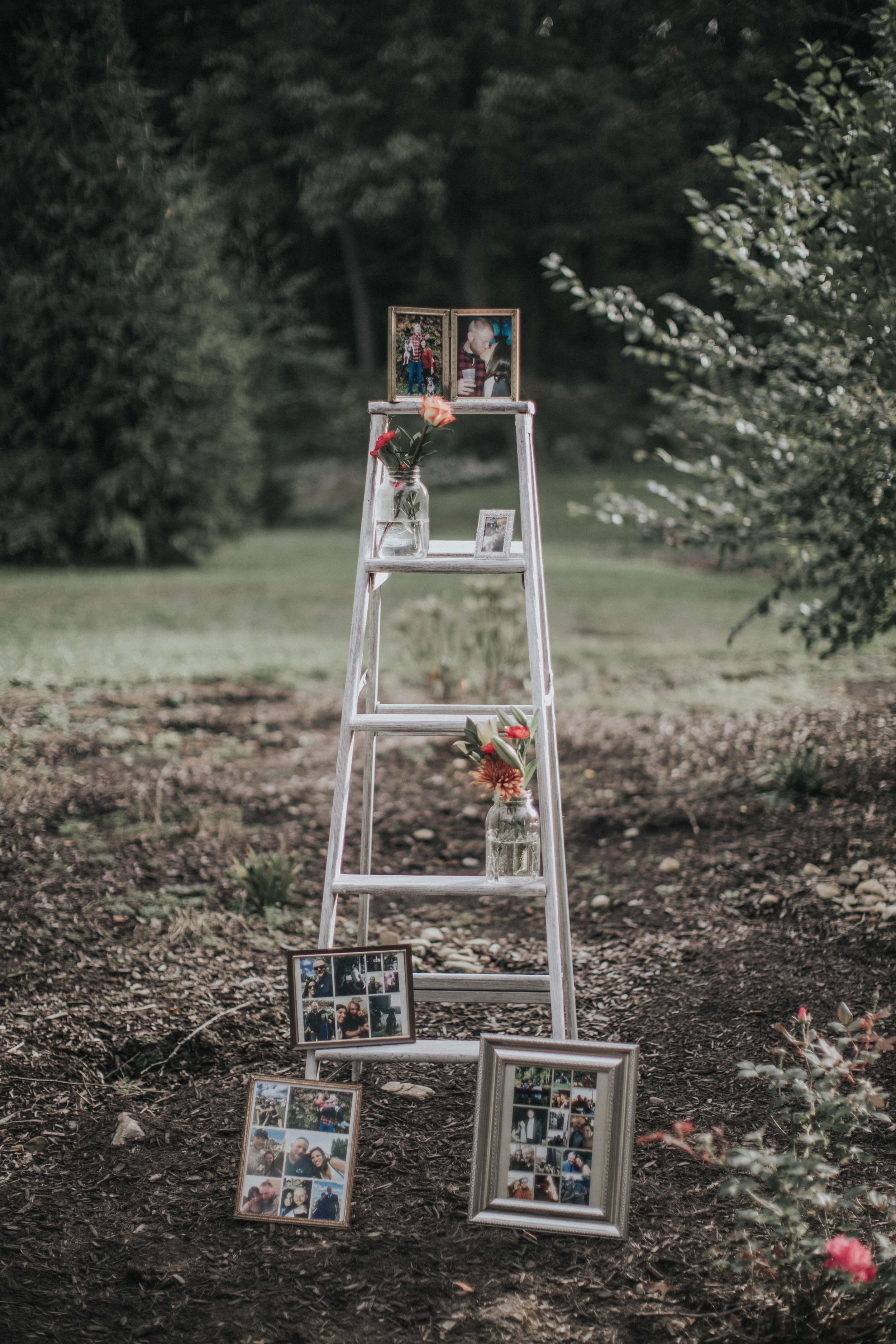 Ladder displaying wedding reception decor in the woods for rustic wedding in Farmington, PA planned by Exhale Events. Find more wedding inspiration at exhale-events.com!