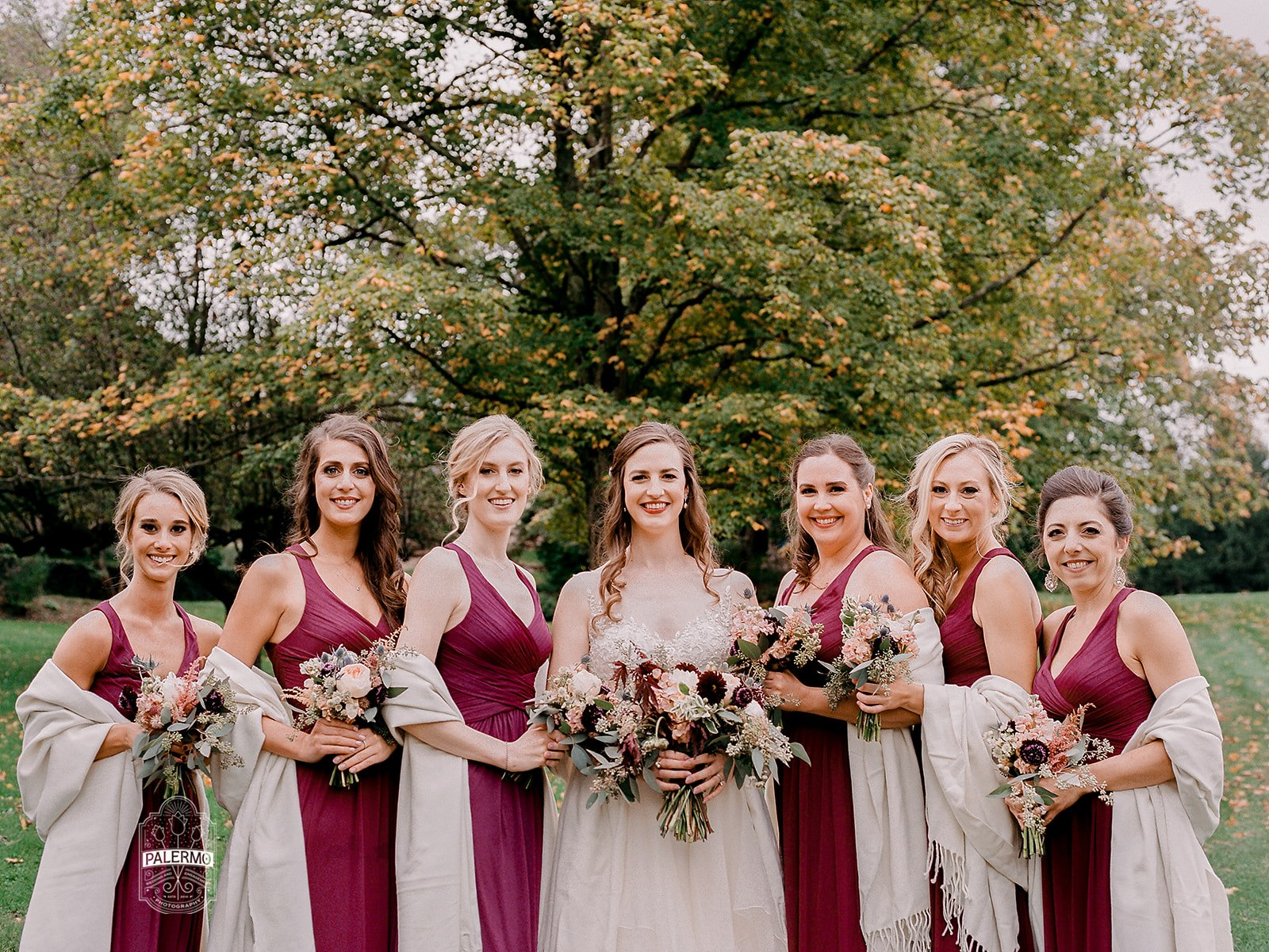 Brides poses with bridesmaids for wedding photos for fall barn wedding in Pittsburgh, PA planned by Exhale Events. Find more wedding inspiration at exhale-events.com!