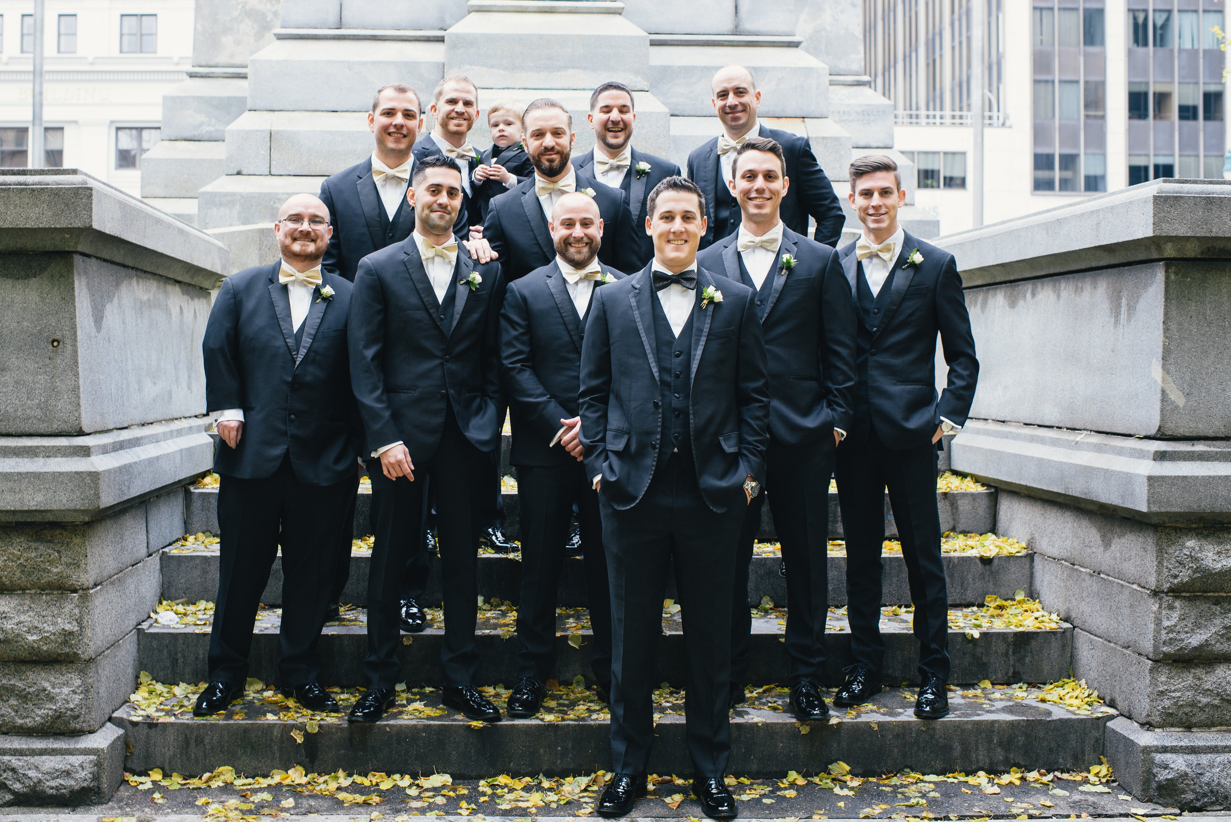 Groom and groomsmen pose for wedding photos in black tuxedos for black, white, and gold wedding in Buffalo, NY planned by Exhale Events. Find more wedding inspiration at exhale-events.com!