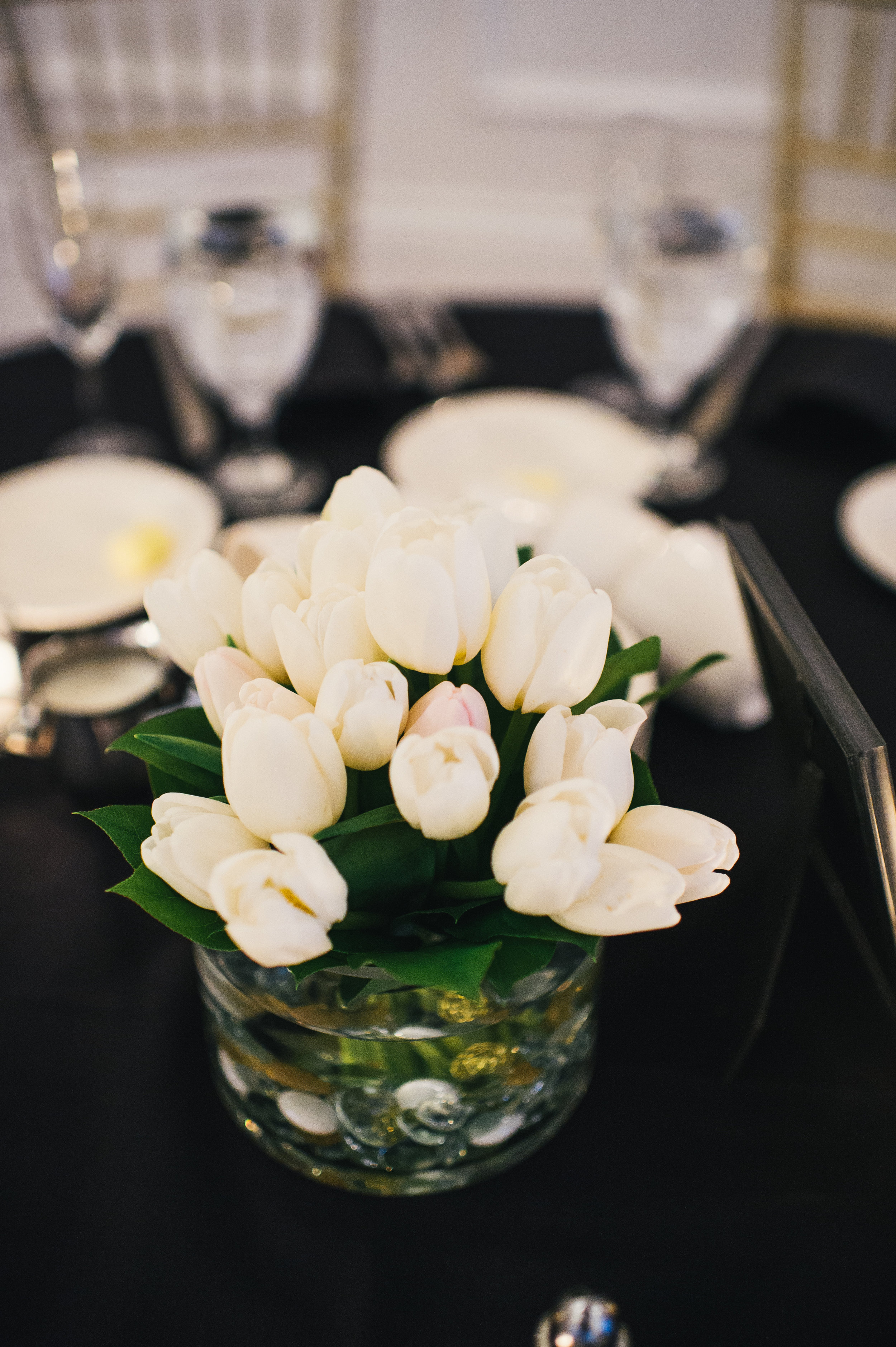 White wedding flower centerpieces for black, white, and gold wedding in Buffalo, NY planned by Exhale Events. Find more wedding inspiration at exhale-events.com!