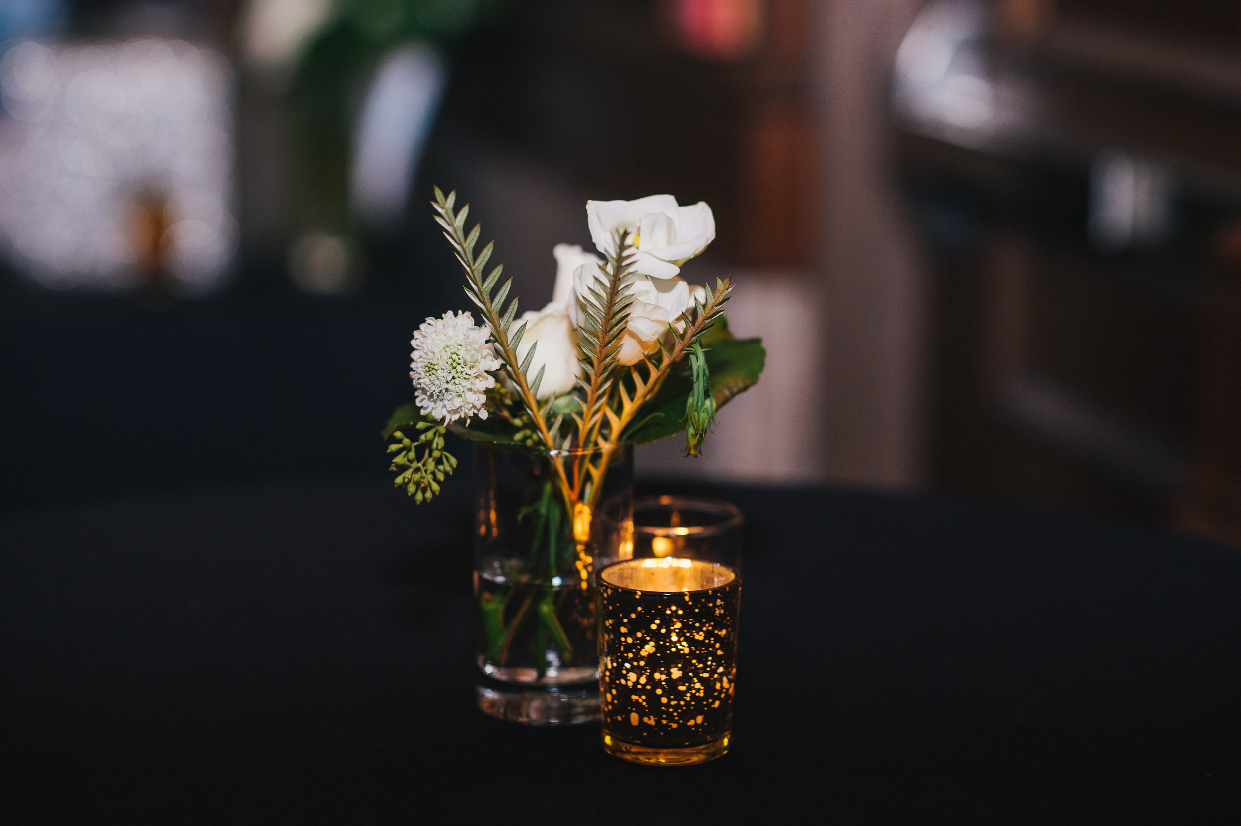 White wedding flower centerpieces with candles for black, white, and gold wedding in Buffalo, NY planned by Exhale Events. Find more wedding inspiration at exhale-events.com!