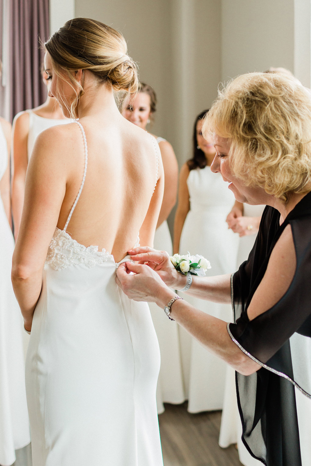 Bride getting into wedding dress for chic wedding in Buffalo, NY planned by Exhale Events. Find more timeless wedding inspiration at exhale-events.com!