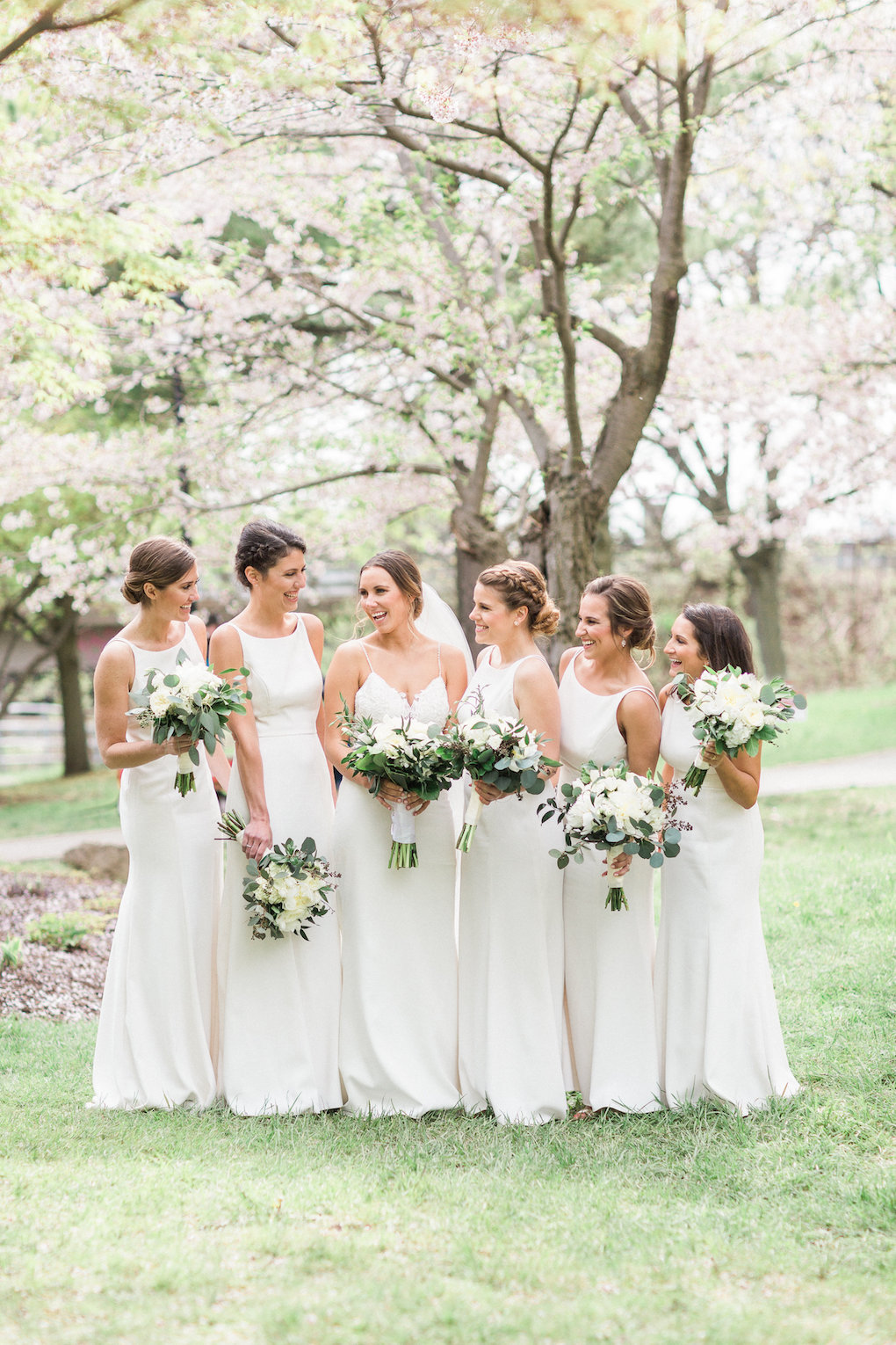 Bridesmaids in white bridesmaids dresses for chic wedding in Buffalo, NY planned by Exhale Events. Find more timeless wedding inspiration at exhale-events.com!