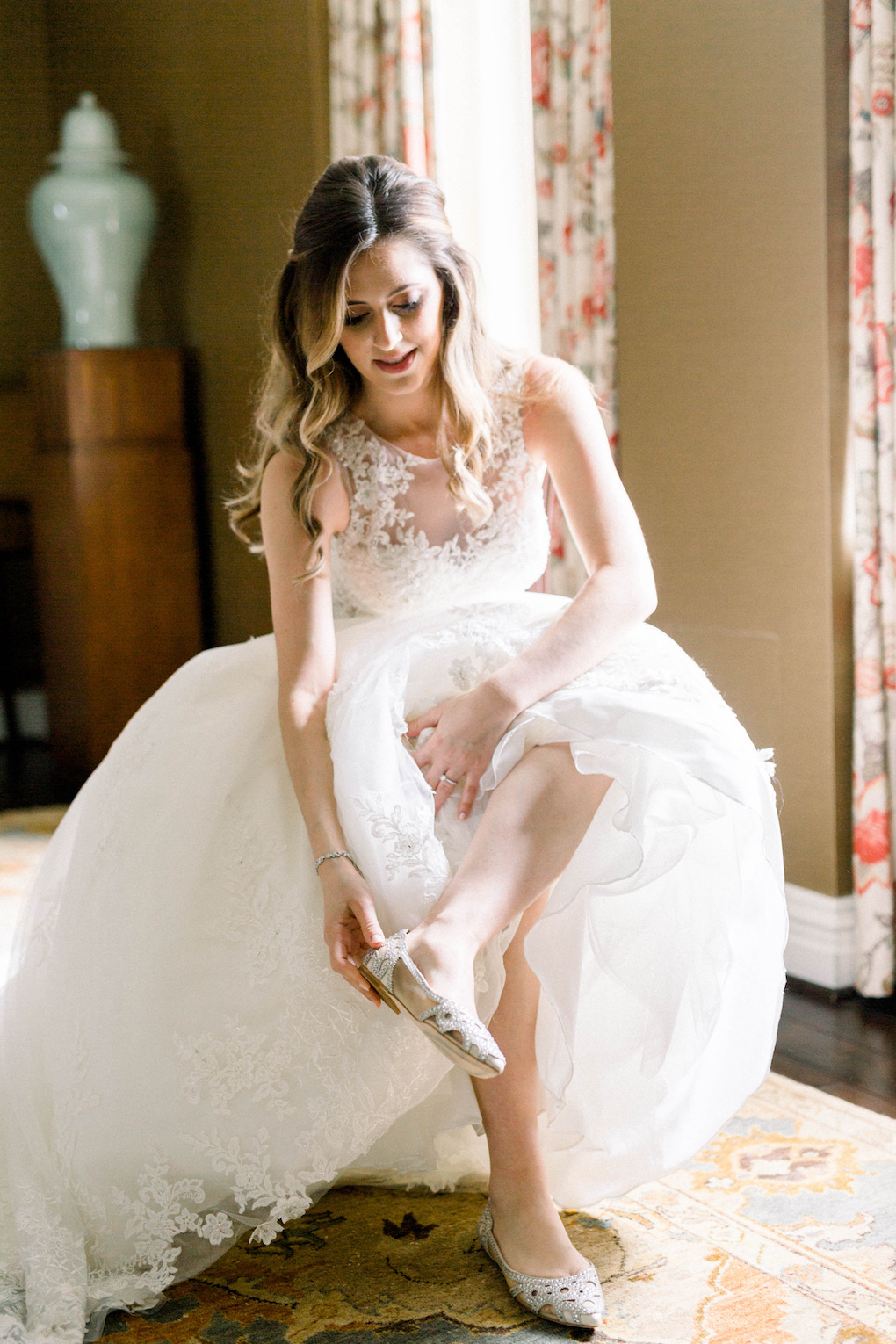 Bride putting on wedding shoes: Romantic Fairytale wedding at the Omni William Penn in Pittsburgh, PA planned by Exhale Events. Find more wedding inspiration at exhale-events.com!