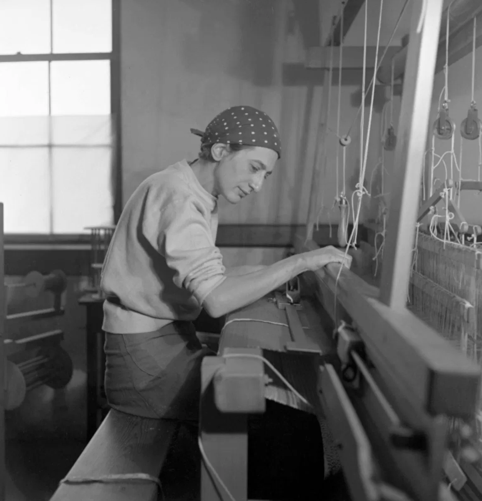 Anni Albers sitting at her loom