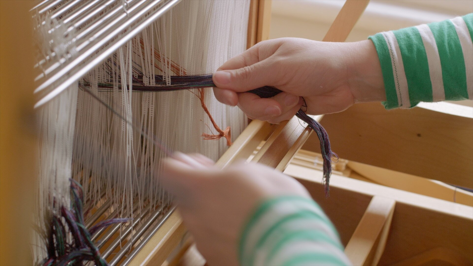 Cecilia of By Cecil threading up her hand loom
