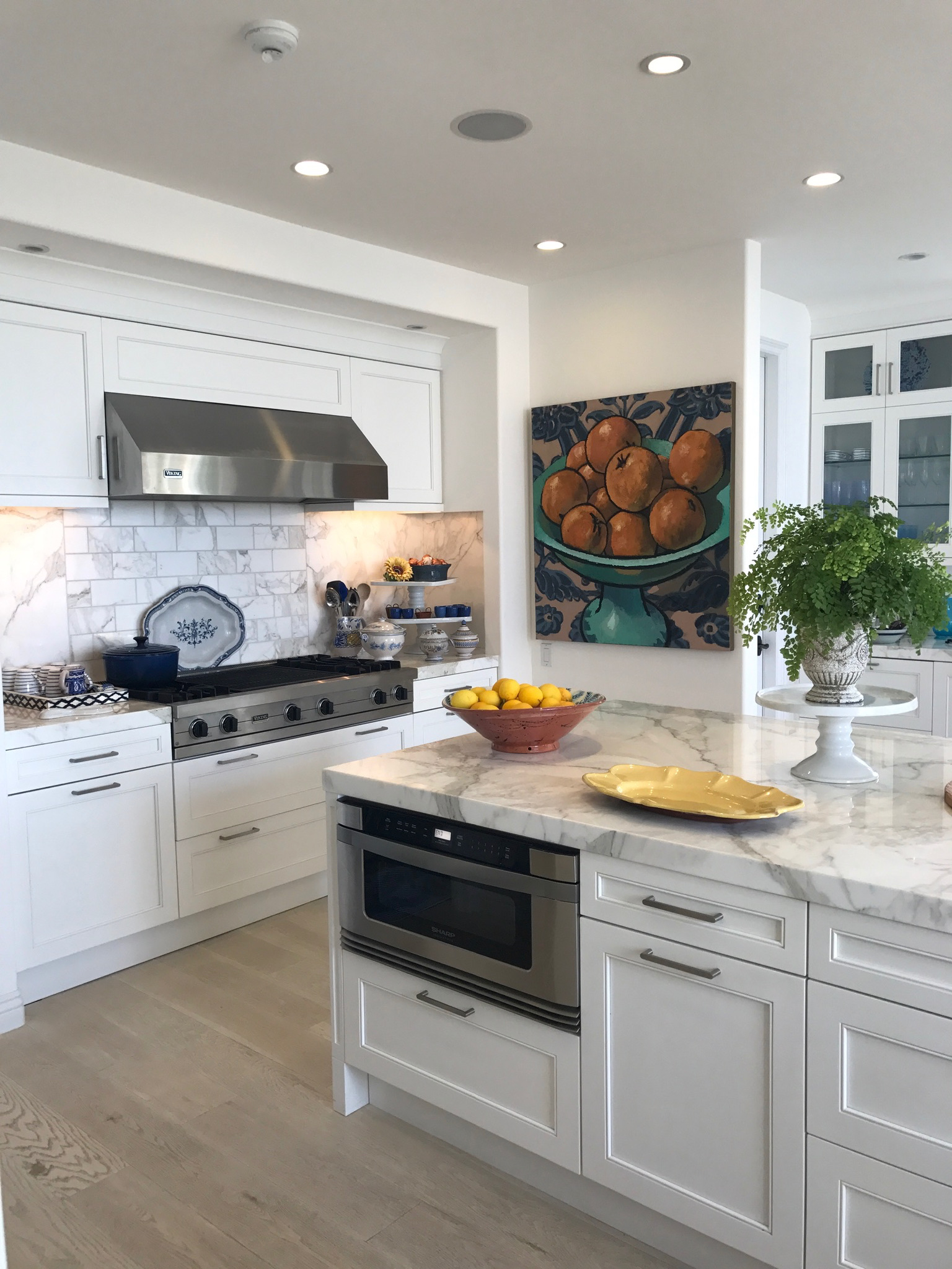 Laguna Beach all white kitchen with wood floors and art.