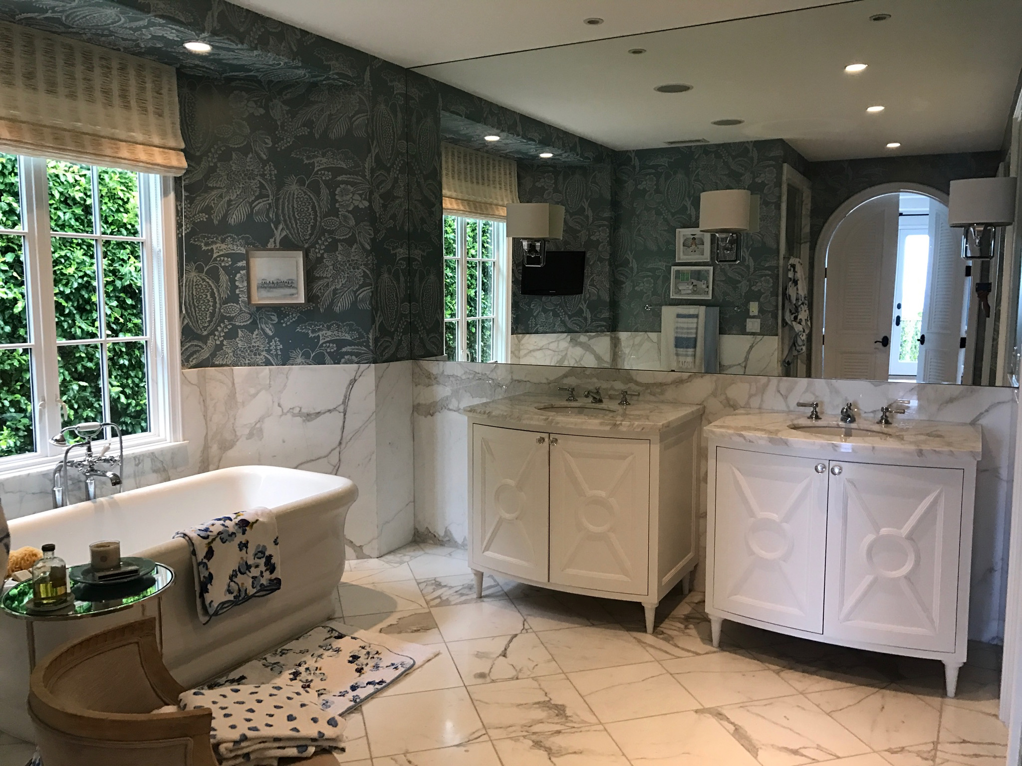 Master bathroom design with blue wallpaper and marble tiled floors. Standalone tub.