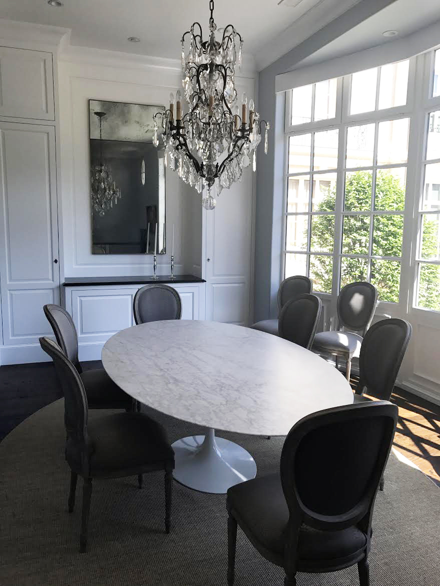 French dining room design with mirror and chandelier, bay windows.
