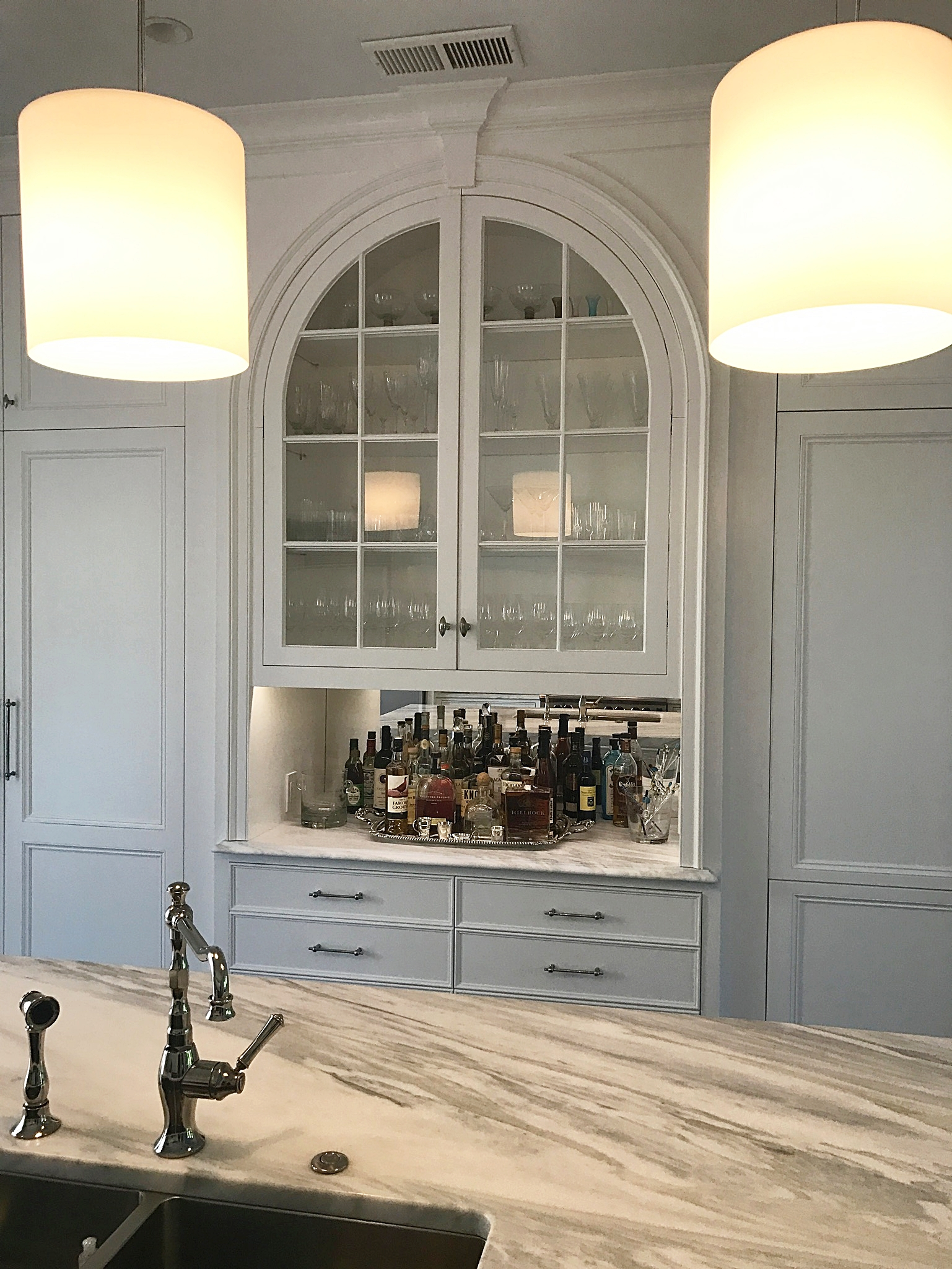 Kitchen bar with marble counters, arched glass cabinets.