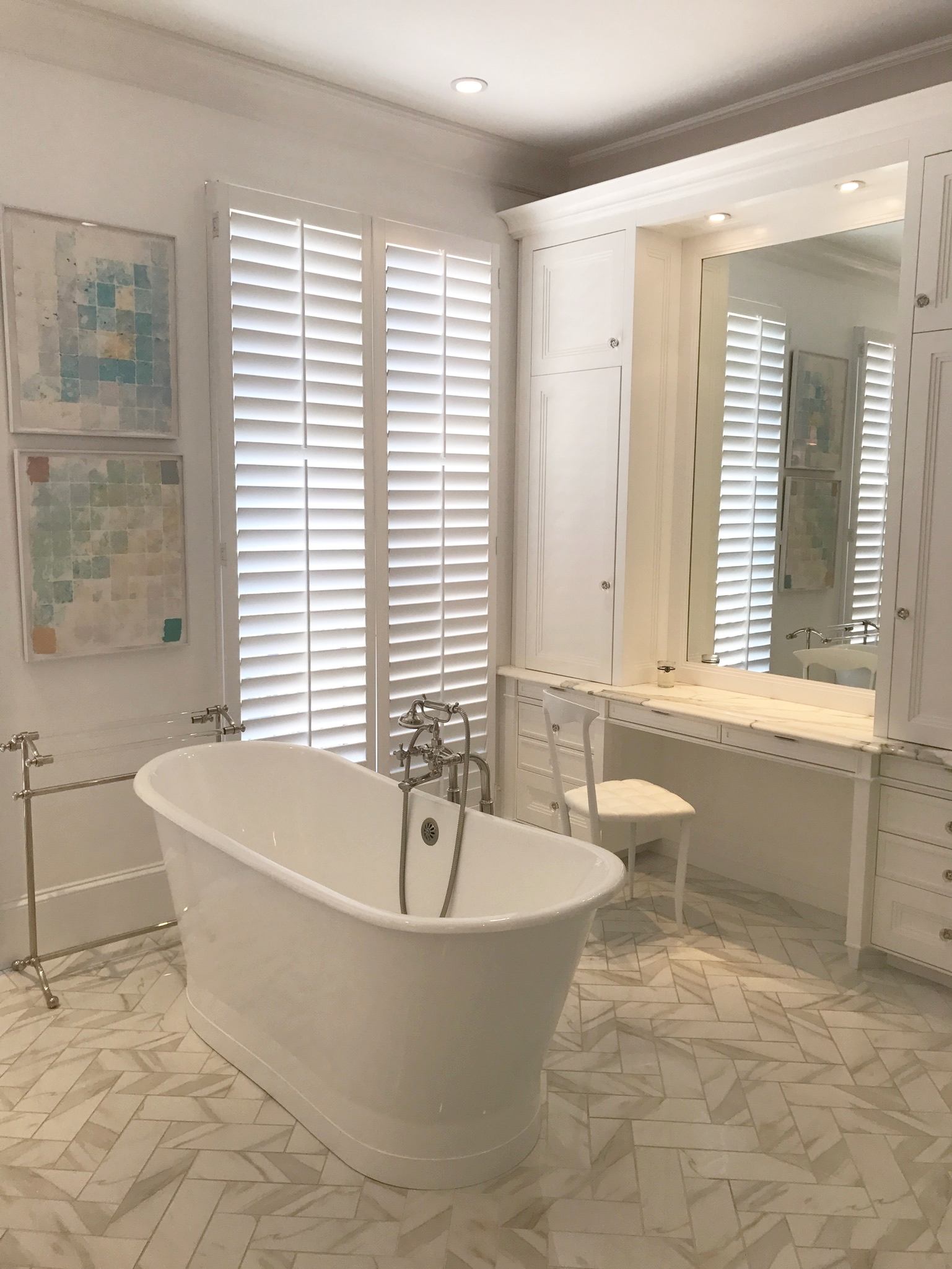 Bathroom design with vanity, stand alone tub, modern art, and tile floors.