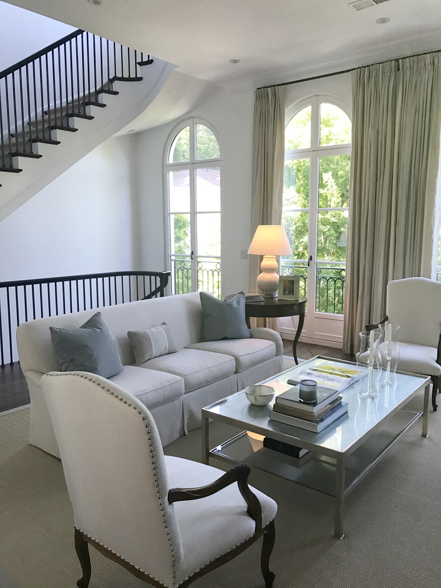 French living room design with spiral staircase and arched window details.