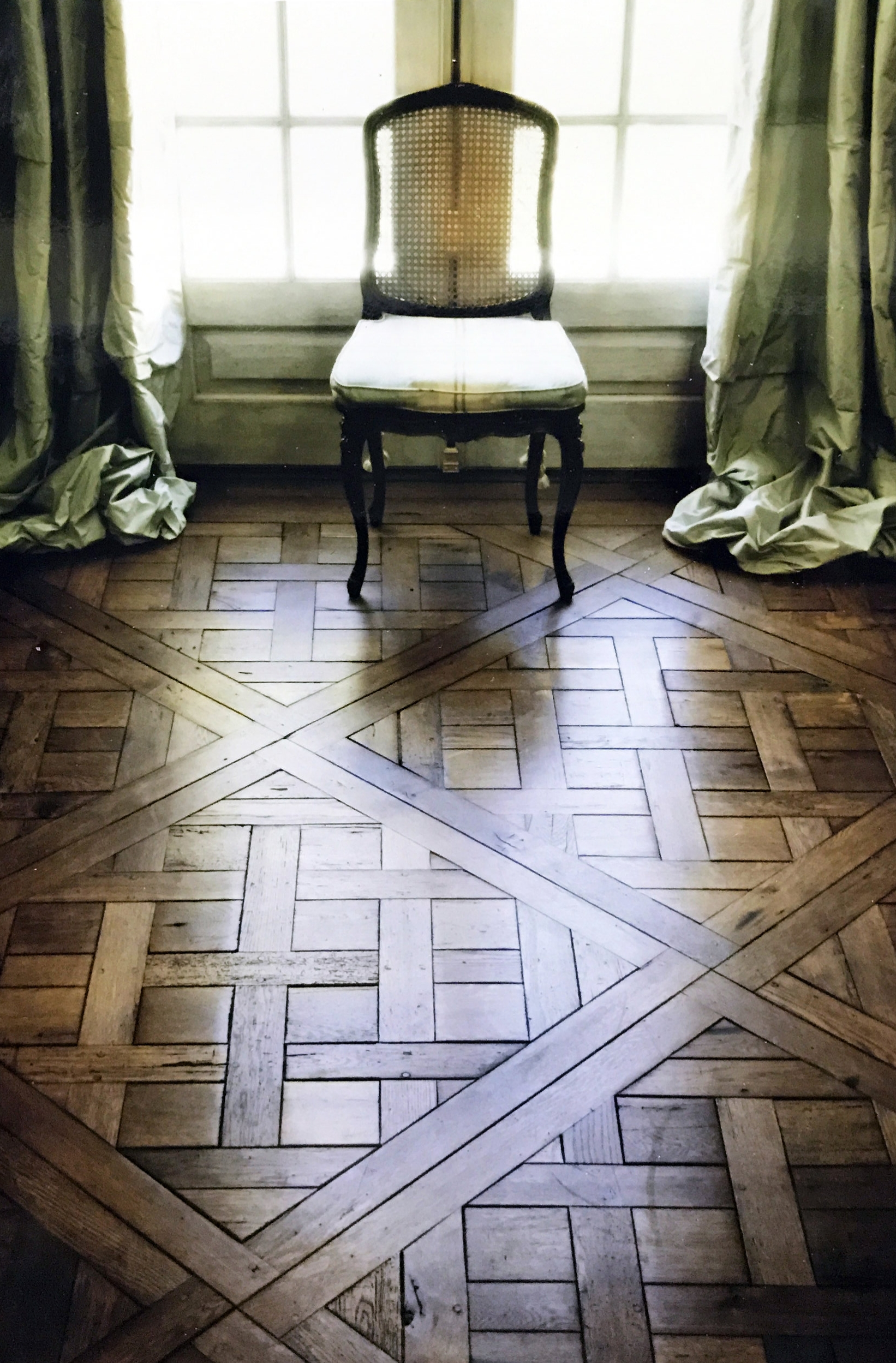 Parquet Floors with chair and window in Parisian style home.