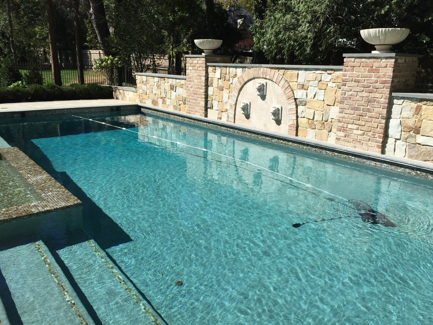 This gorgeous in-ground pool features glass tile, gas fire bowls, LED bubbler fountains and more.