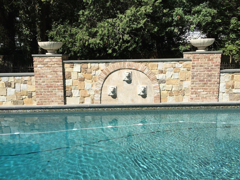 60' raise beam privacy wall - brick columns - gas fire bowls - lion head fountains -