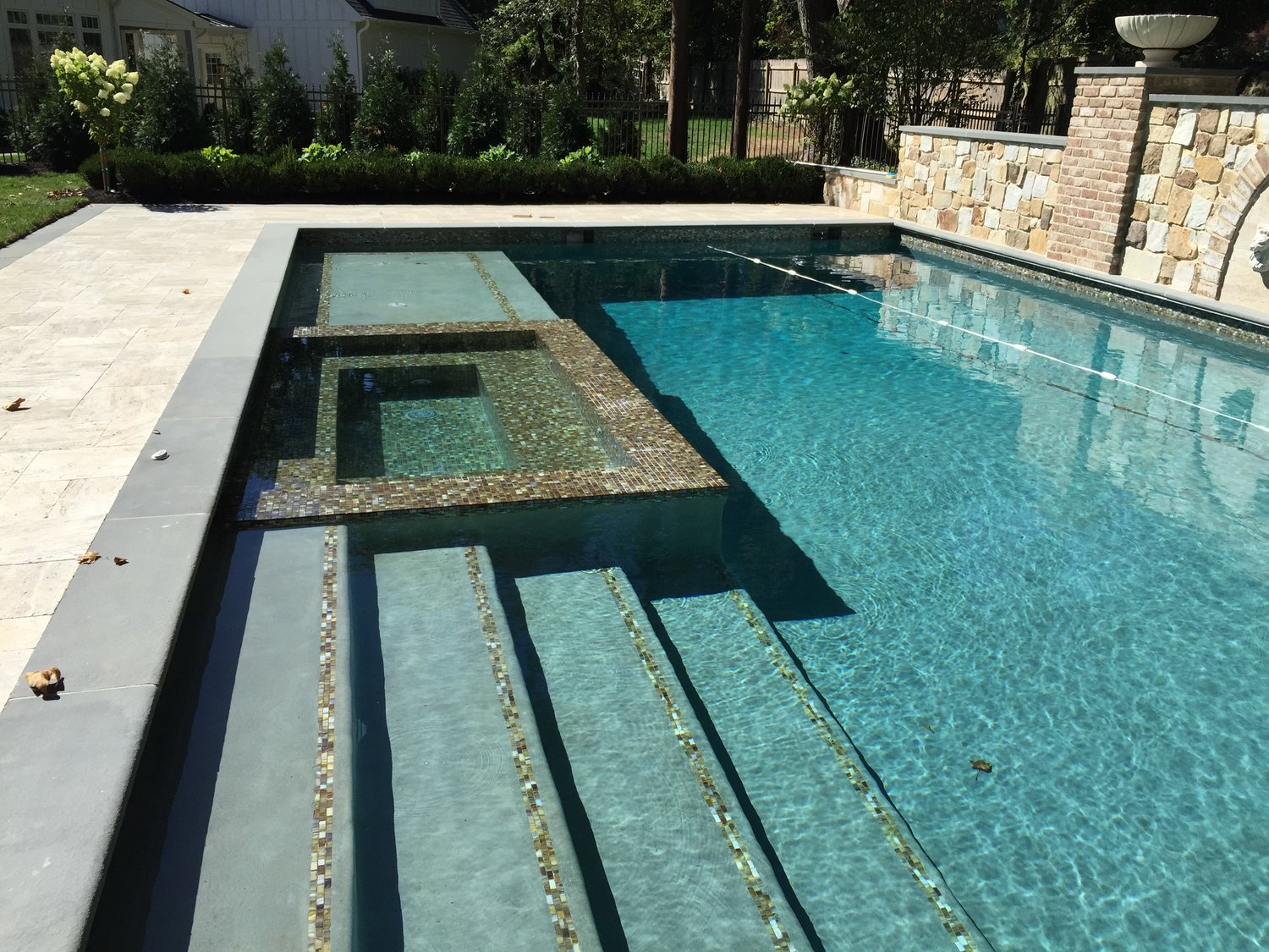 25' x 45' pool with grand entry steps - all glass tile interior spa - blue stone coping - travertine patio