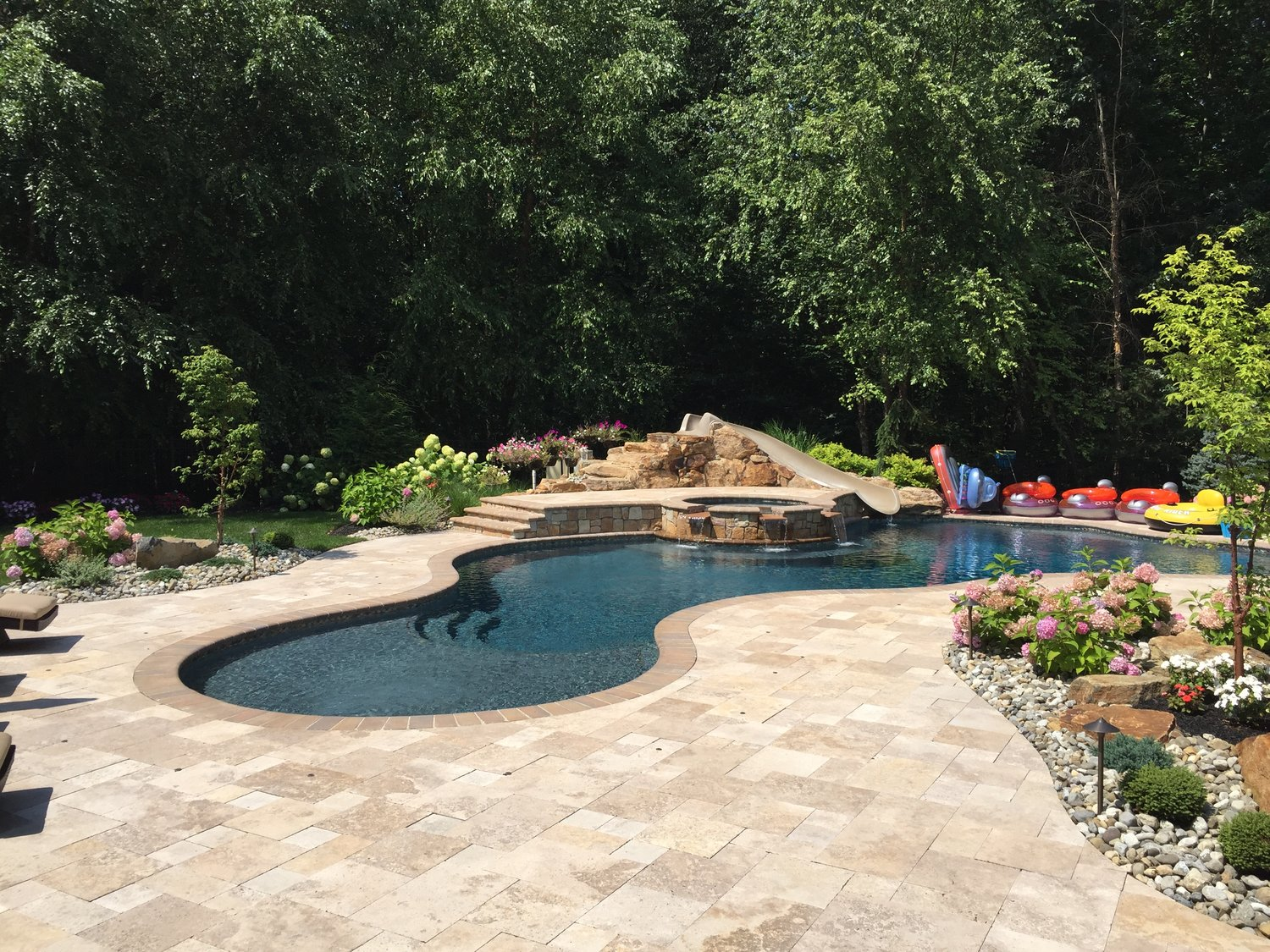 Tuscany in Montville - 825 sf free form pool - 125 sf sun shelf - tumbled brick coping - travertine patio - raised spa with triple spillways -stone veneer 0 17' waterslide with custom stone steps - gas fire pit - outdoor kitchen and bar - mediterranean blue hydrazzo plaster finish - glass tile - LED lighting
