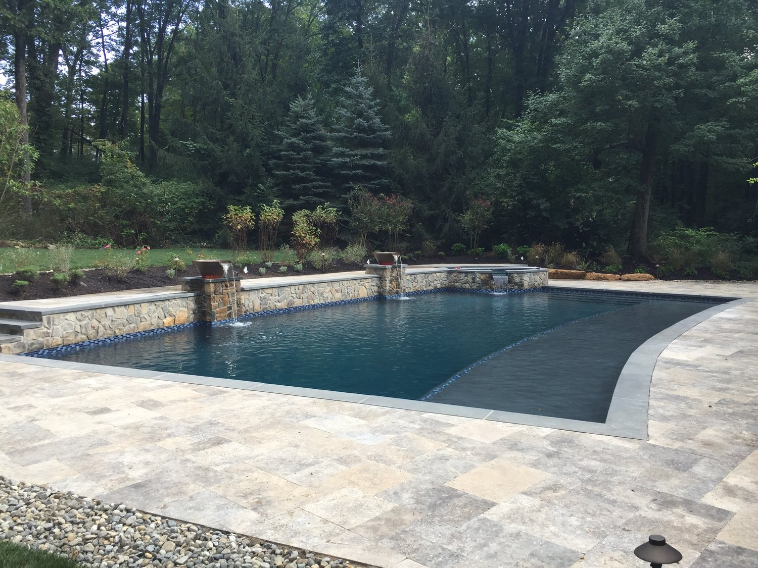 Perfectly set in this serene environment, this custom pool contains magic bowls, 45' sun shelf, and raised octagonal spa.