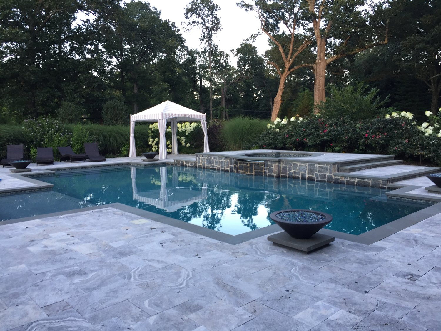 Morristown Transitional - 20' x 44' pool - sun shelf - raised quatrofoil spa - sheer descent waterfalls - blue stone coping - travertine patio - granite raised beam wall - hatteras gray hydrazzo plaster finish - fire bowls - LED lighting