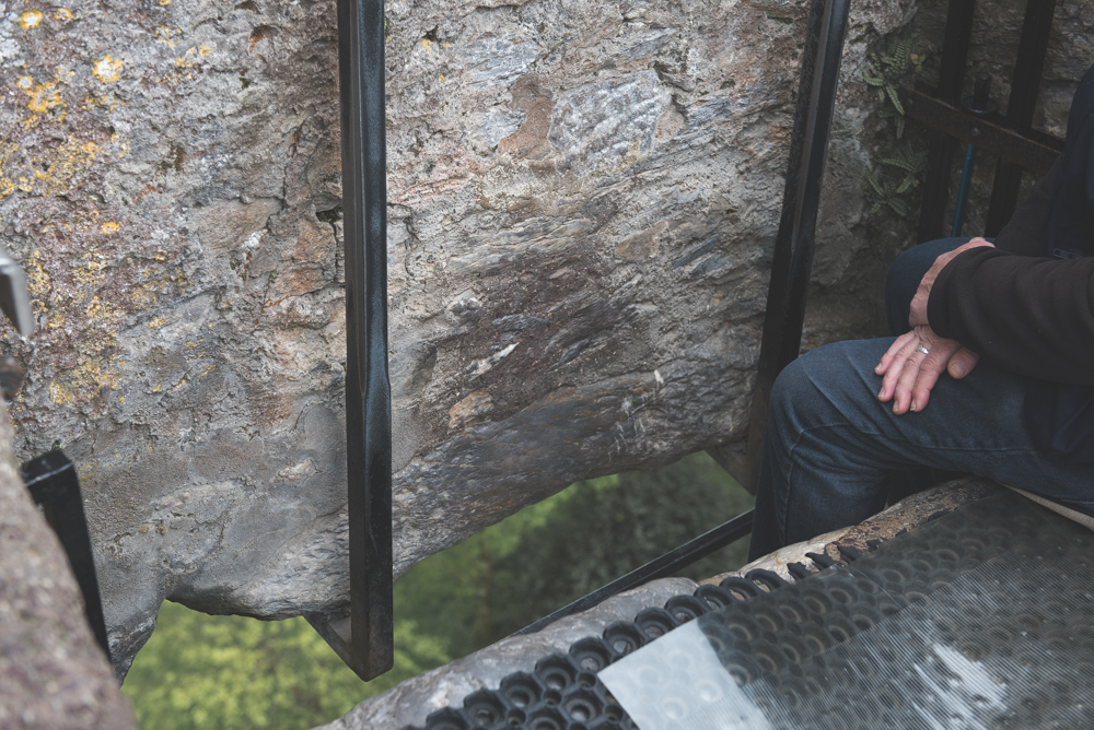 Kissing the Blarney stone is said to bestow you with the gift of eloquence.  This gentleman is responsible for lowing each person down to kiss the stone.