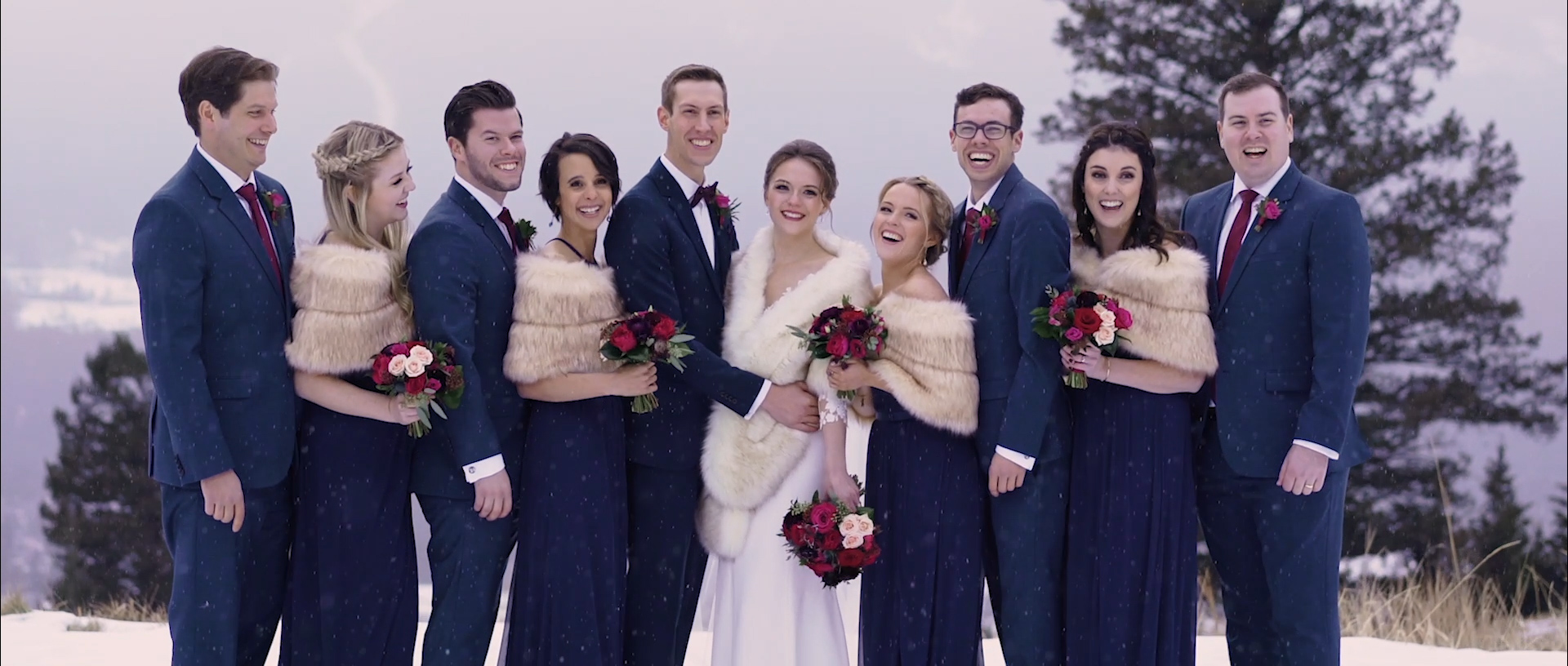 The bride + groom and their attendants having a great time as the snow falls!