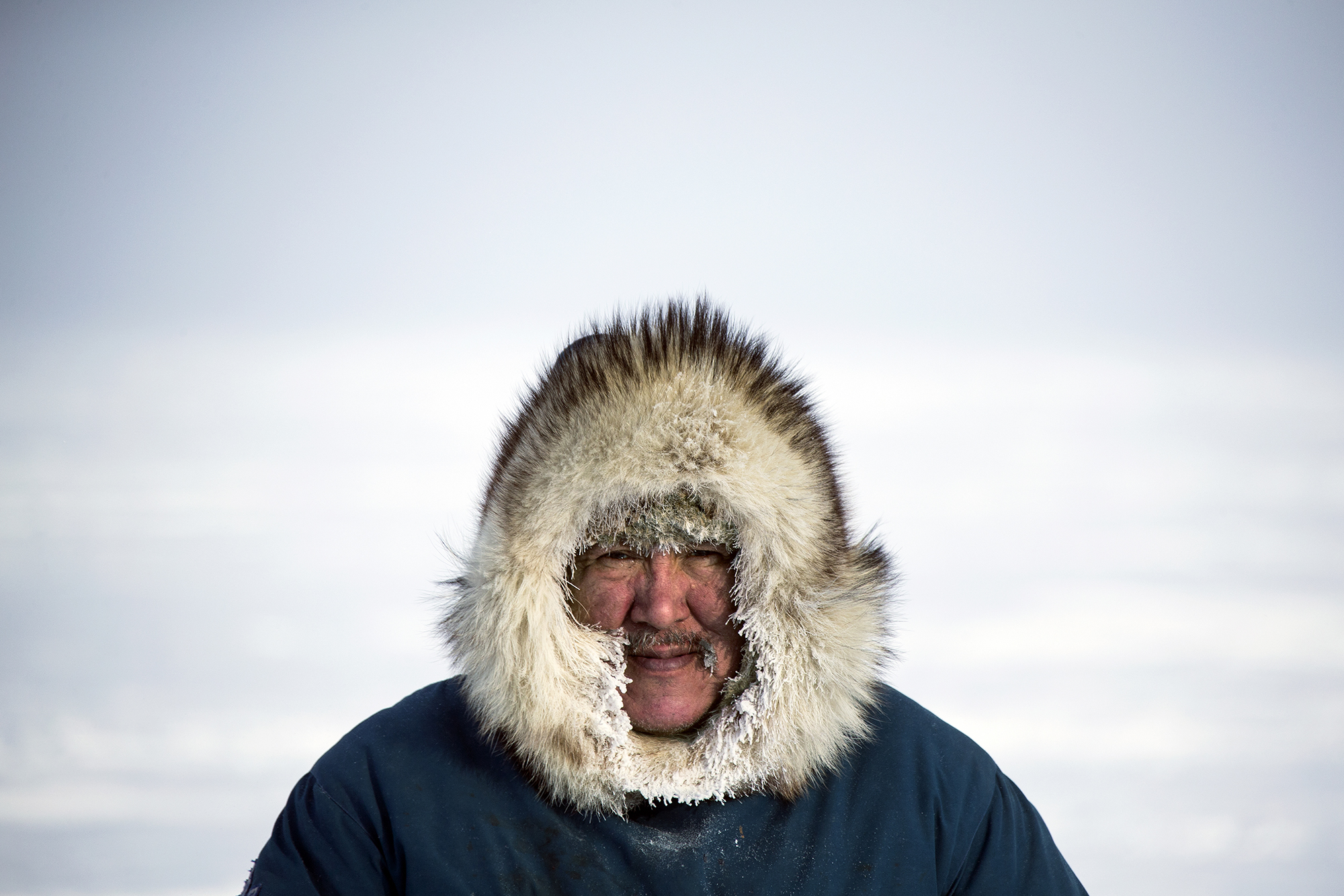 A Canadian Inuit man on the sea ice in the winter. Hall Beach, Nunavut, Canada.