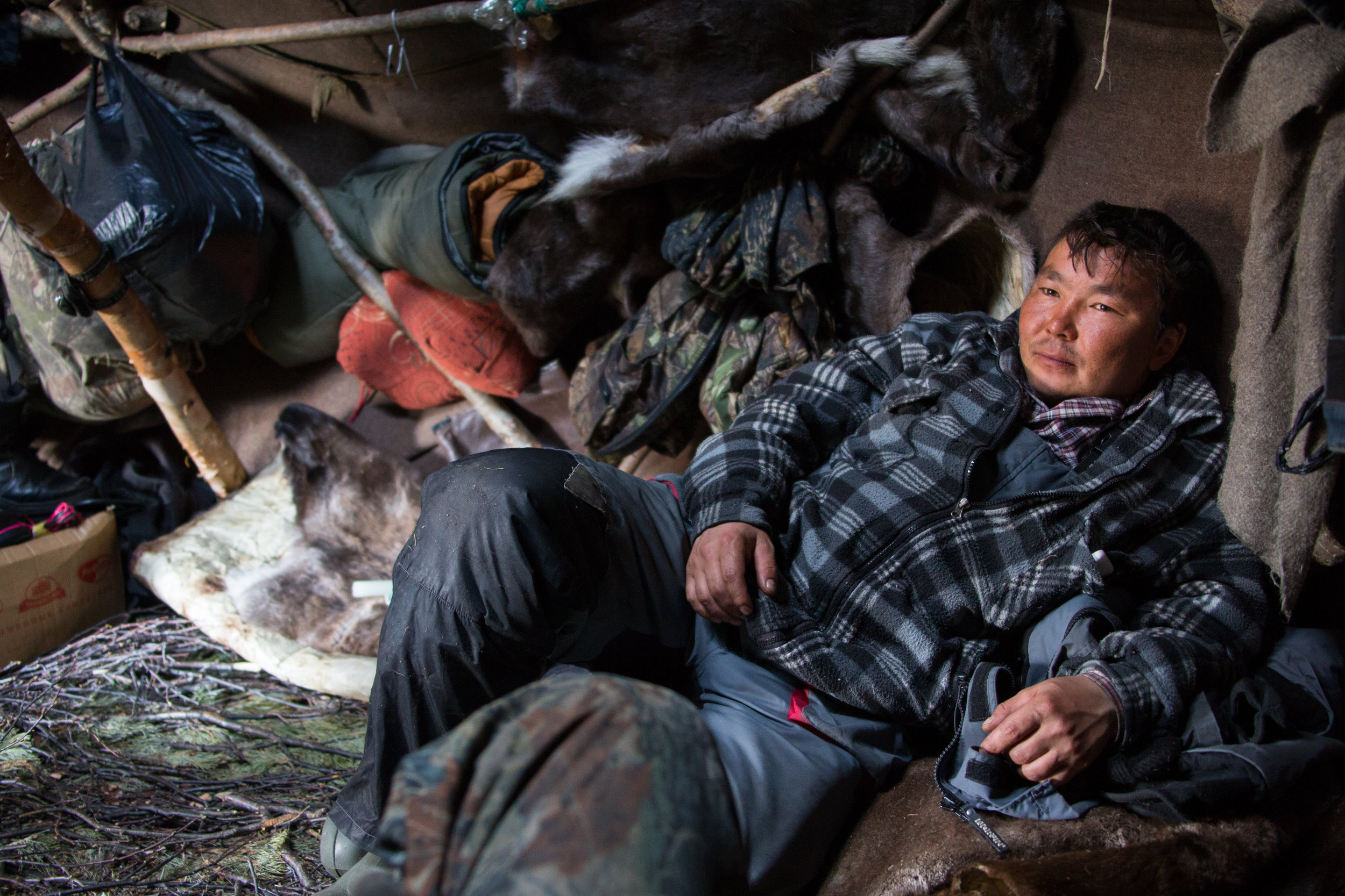 An Even reindeer herder takes a break in his winter yurt in the Kamchatka backcountry. Ichinsky District, Kamchatka, Russia.