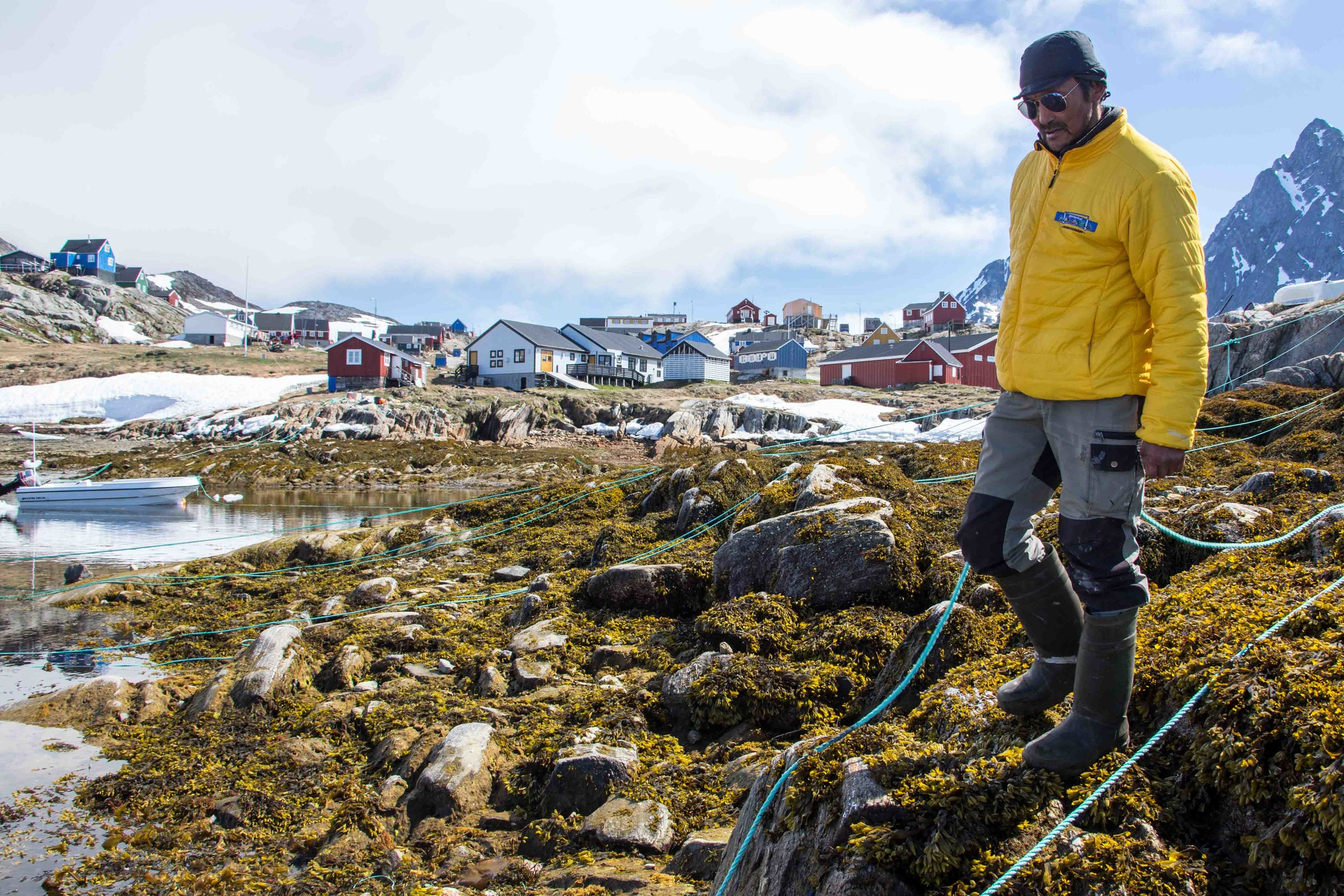 A Greenlandic fishermen just finished tying his boat line to the shore in the settlement of Kuummiit, East Greenland.