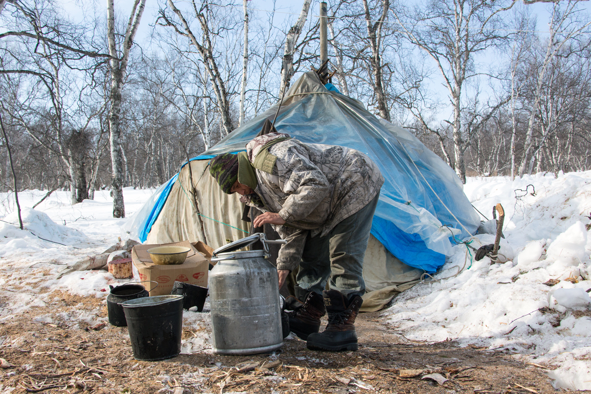 One of the reindeer herders refills the water kettle outside the yurt. Photo: Matt Reichel.