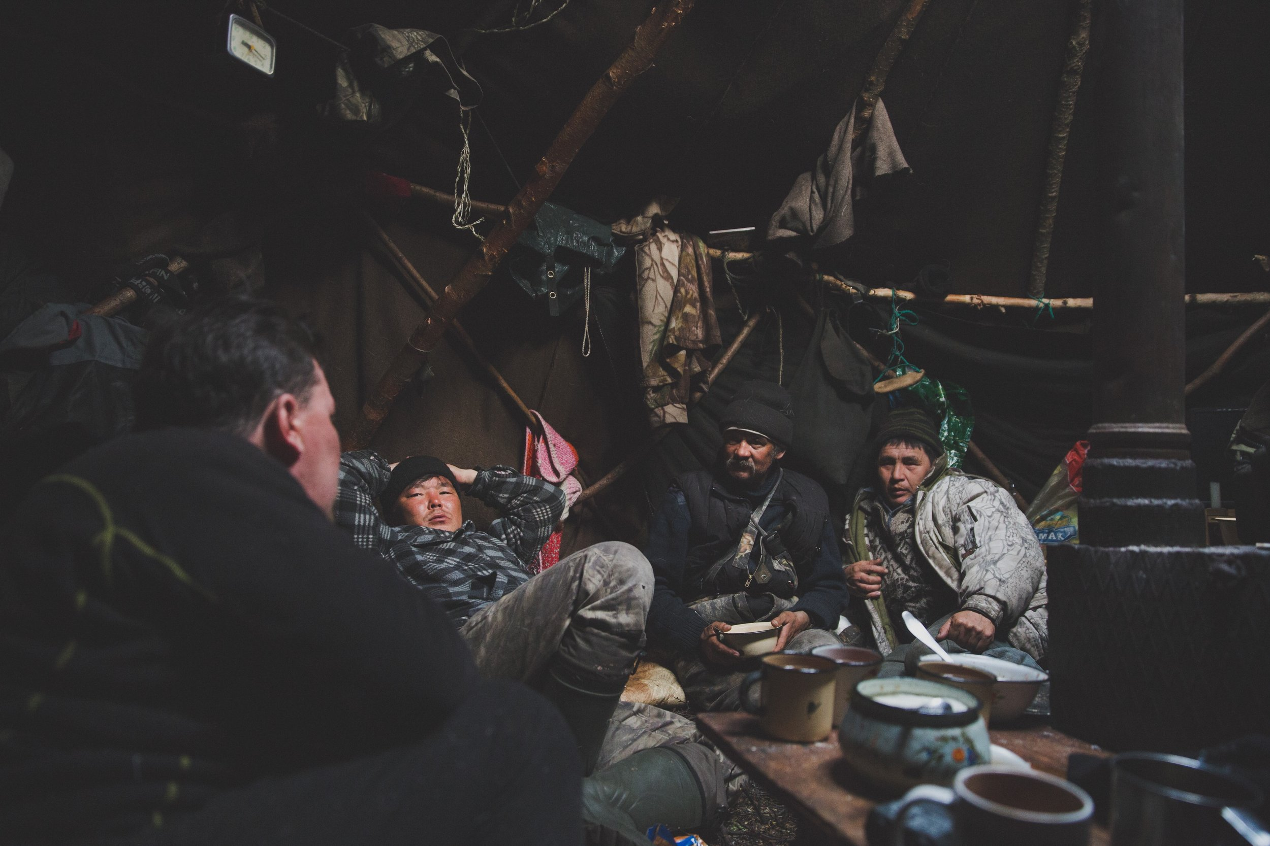 Reindeer herders along with some members from our Russian team relax in the winter yurt.