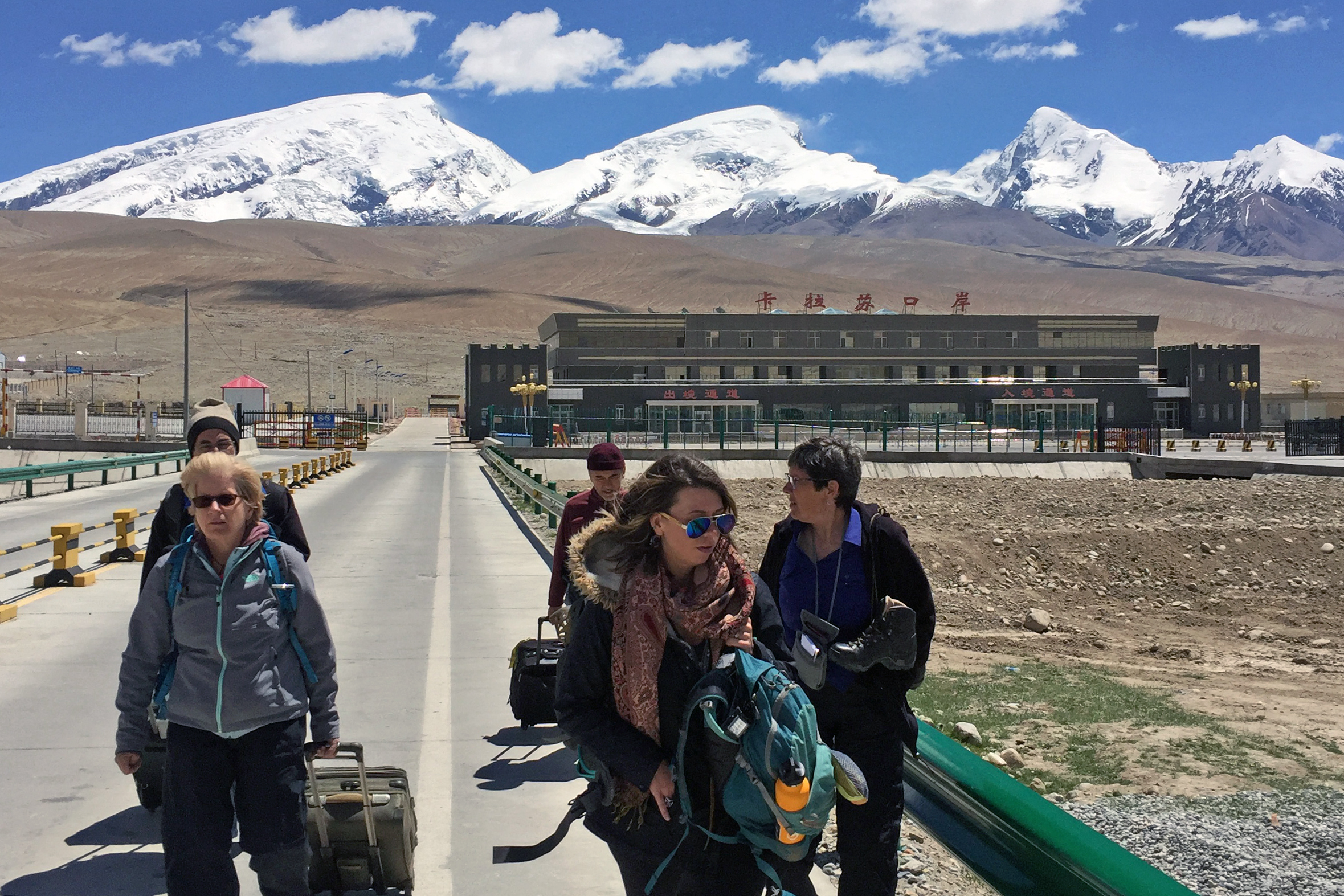 Tourists walk past the Kalasu Customs Port in China on their way to Tajikistan.