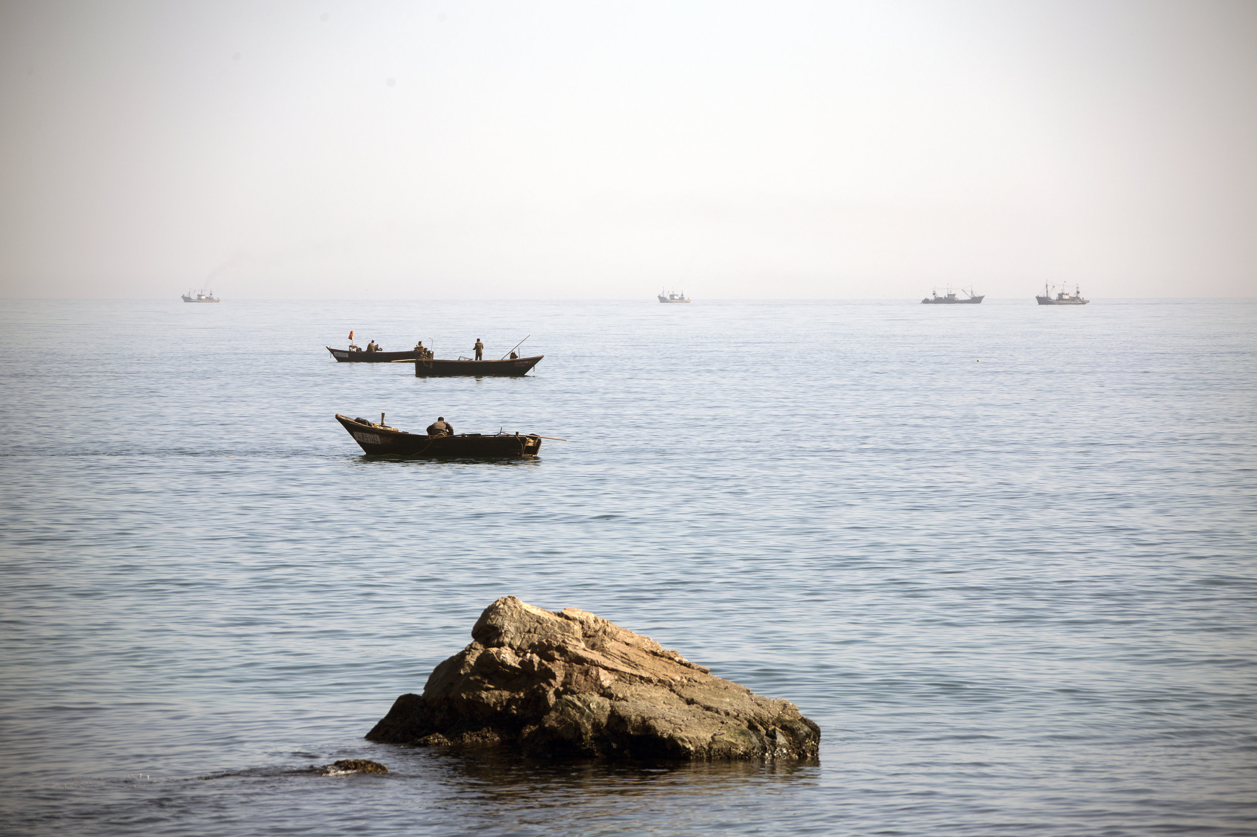 Local fishermen use wooden boats and lines to catch small fish off the coast of North Hamgyong.