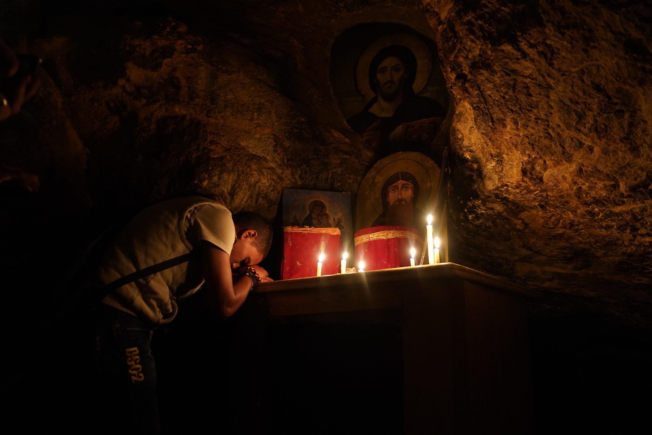 A Coptic pilgrim prays in the cave of Saint Anthony.